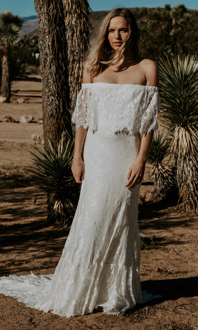 LAURENCE features an eyelash lace off the shoulder wedding gown. It speaks to our bohemian bride on the hunt for a more classic lace option. LAURENCE shows a fitted bodice to accentuate the waist and a fit and flare skirt. A full rounded cascading train completes the look.