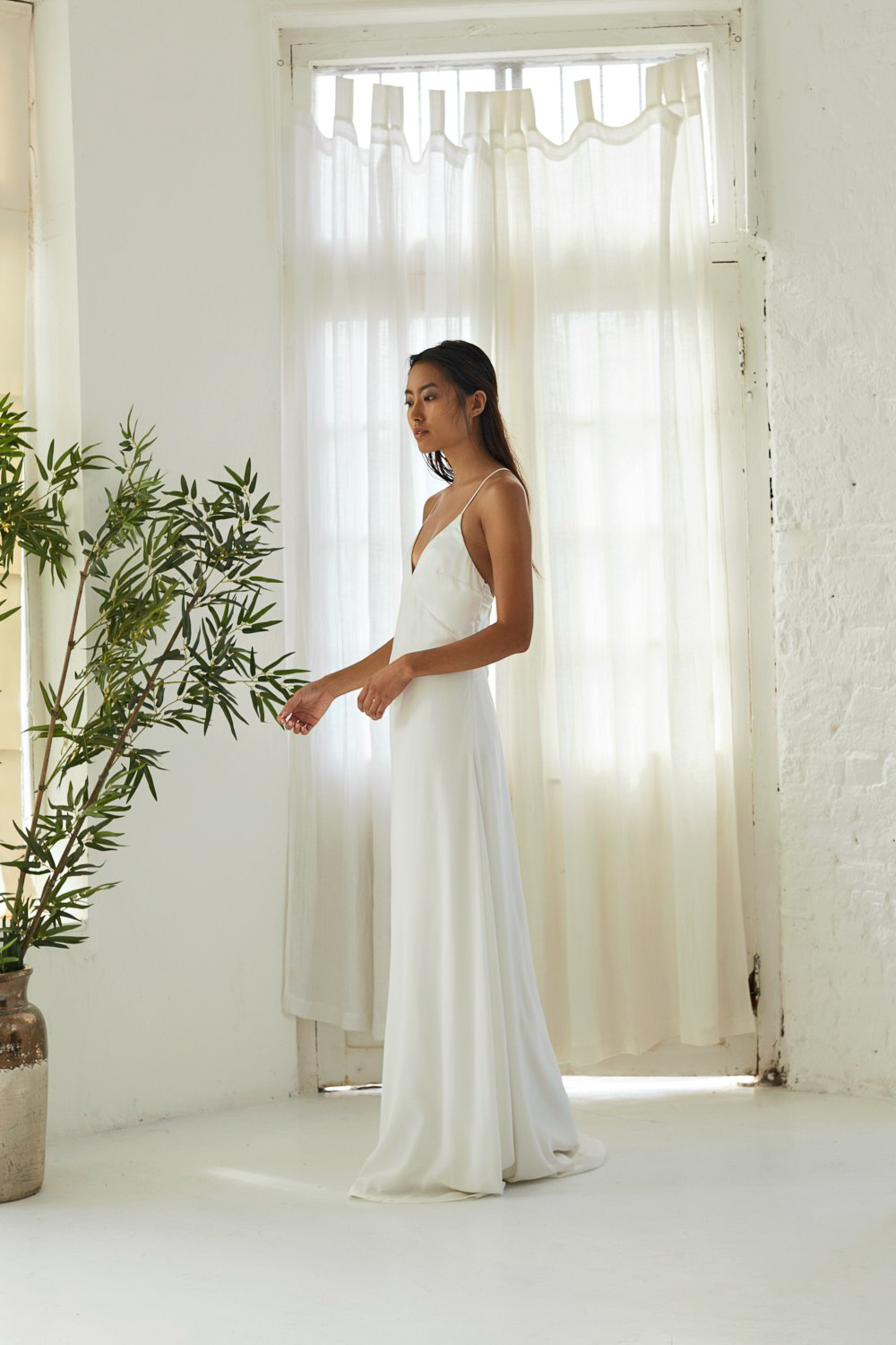 ANAIS GOWN – The ANAIS wedding dress epitomizes effortless elegance. This slip style wedding gown features under bust seam detailing and thin bias straps that cross over the low back. The subtle V-front bodice is semi fitted around the bust and falls softly down to a loosely skimming liquid silk skirt.