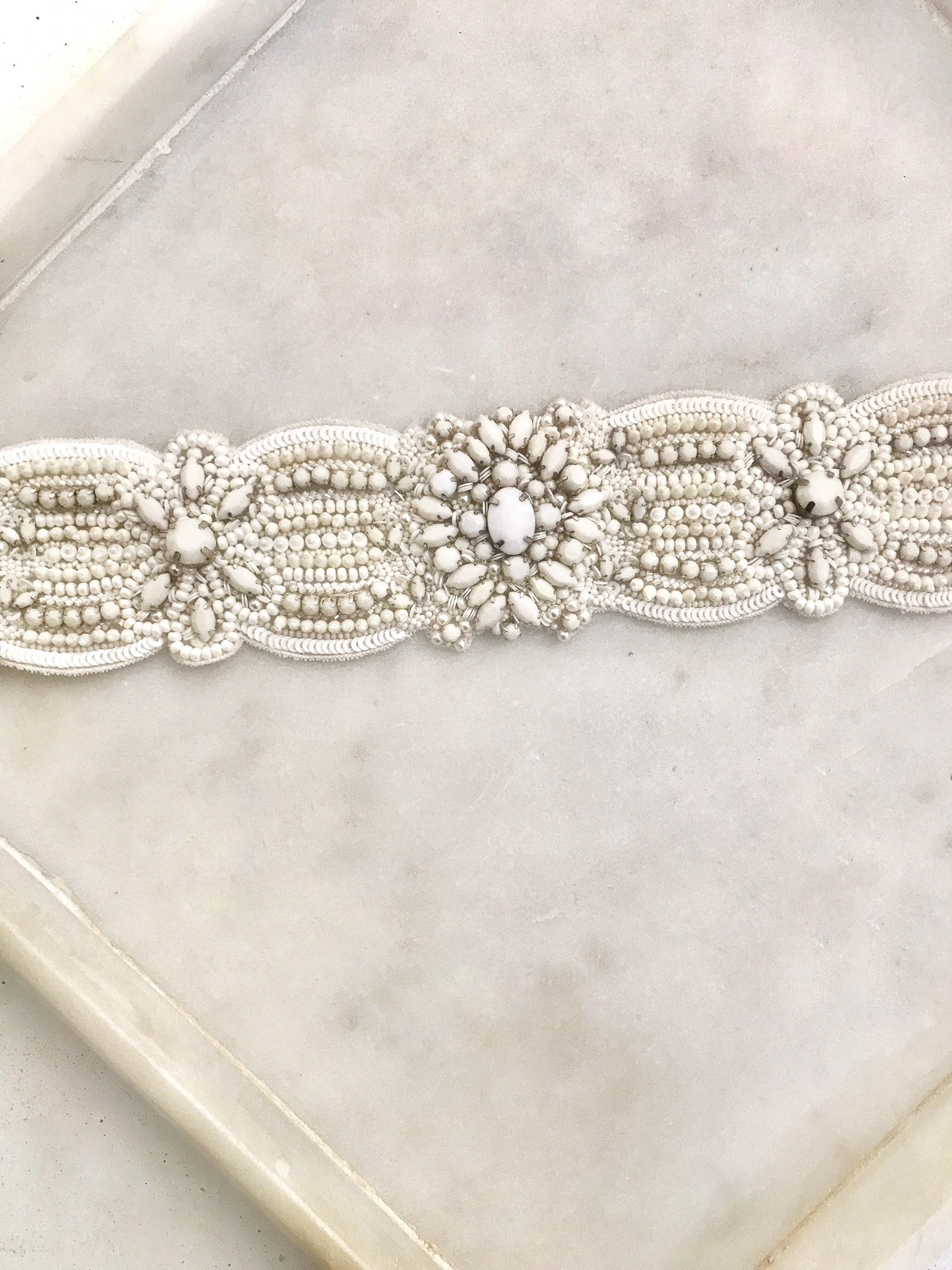 CASABLANCA BELT – This statement wedding belt features oversized crystals and off white stones that have been delicately hand woven onto silk. To be worn around the waist and ties with a silk ribbon around the back.