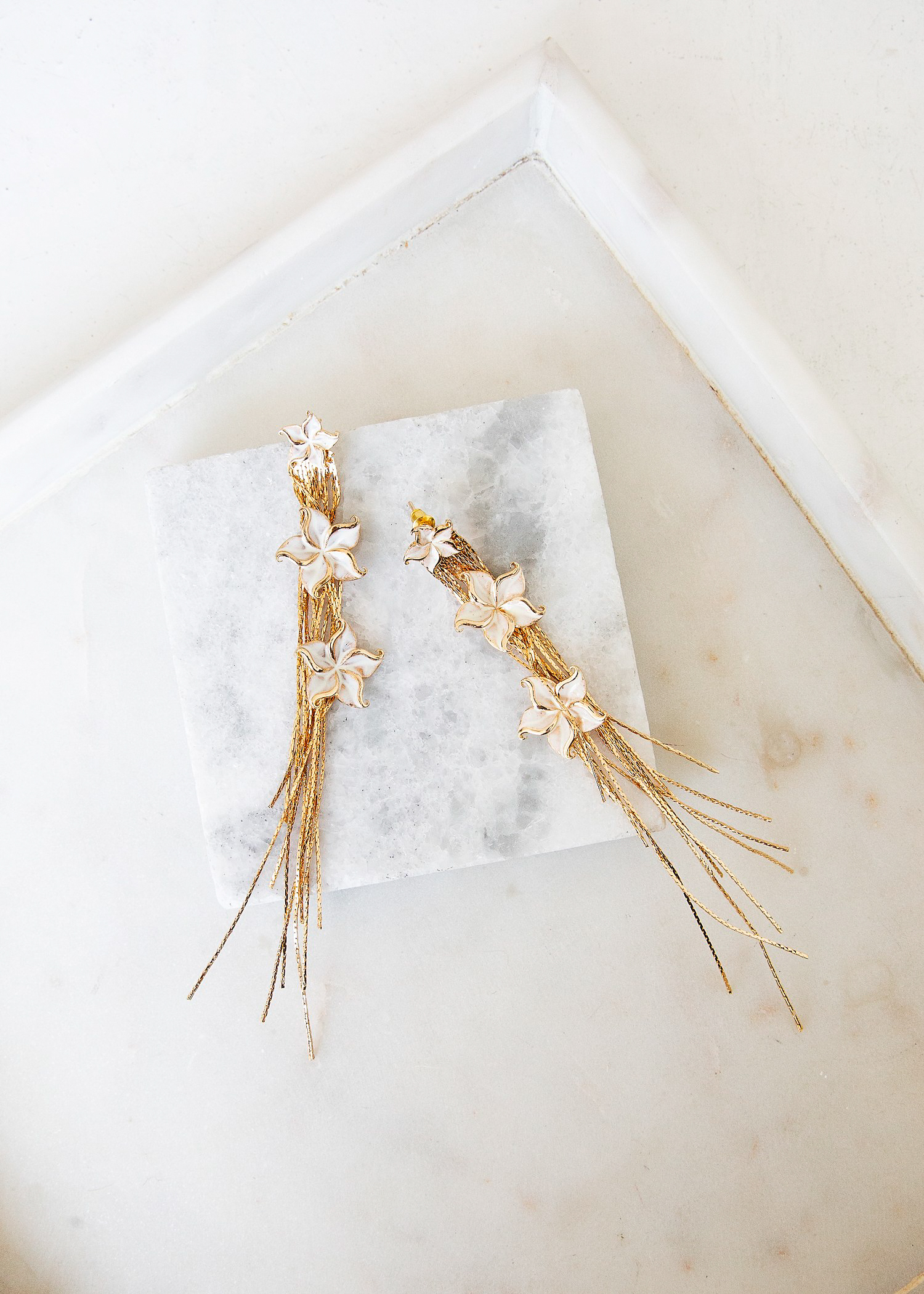 EDEN EARRINGS – The delicate Eden drop earrings are the perfect look for the contemporary bride on her wedding day. Cascading gold stands and three tiers of off white florals that frame the face.