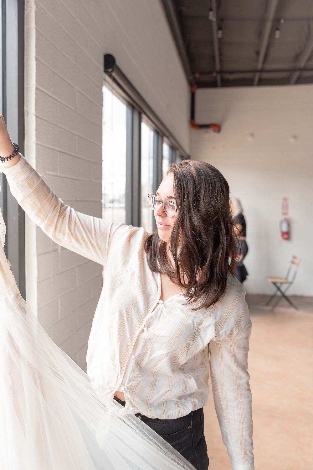 A little BTS shot of Owner and Creative Director of Neue Bride, Sydney getting the dress ready.
