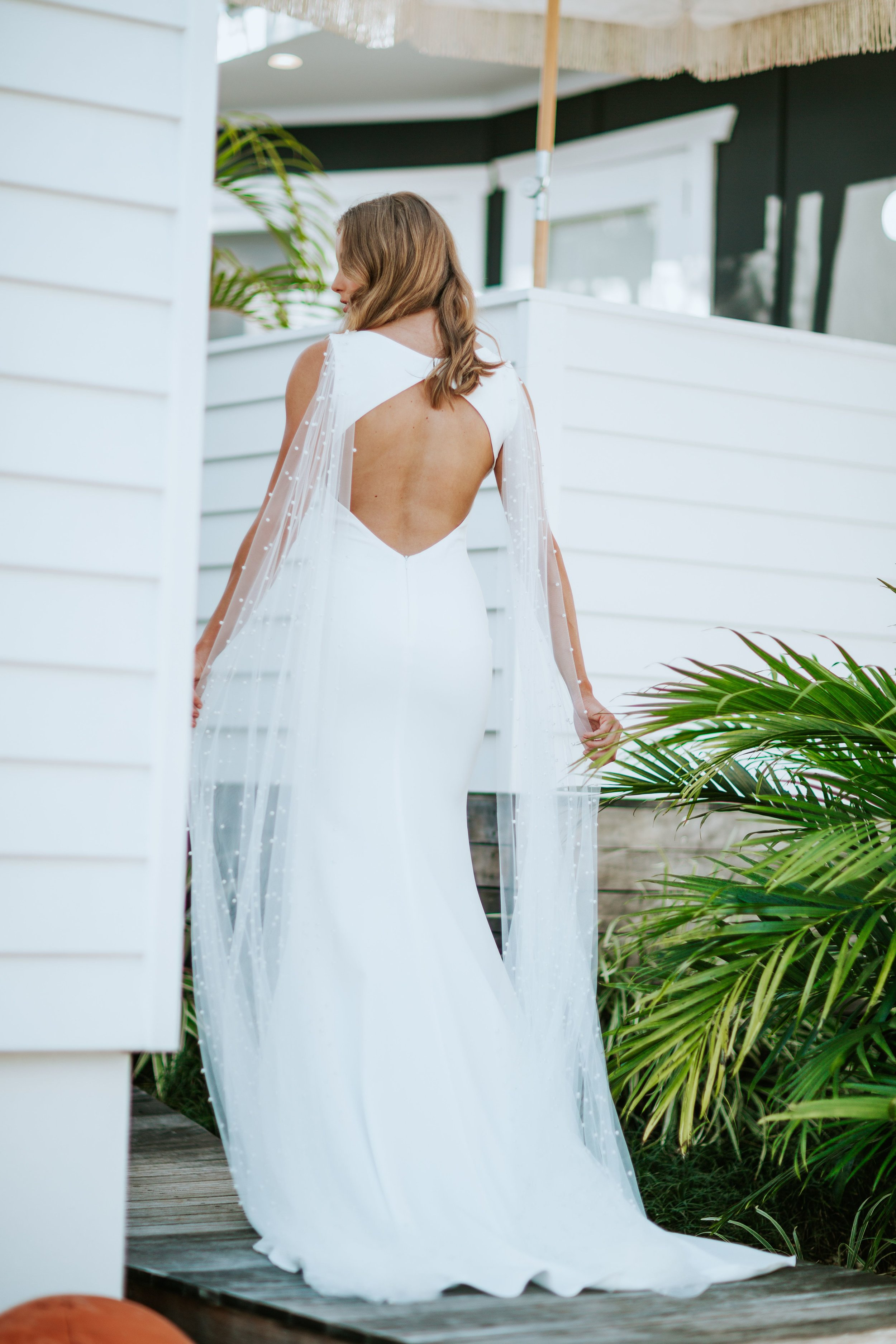 PORTUGAL was designed to cater to the versatile, modern minimalistic bride who wants it all. Her desires are ever-changing – as is this unique gown. This clean matte French crepe silhouette has multiple accessory pieces that can be added for different looks (detachable pearls, veil capes or lace trim)