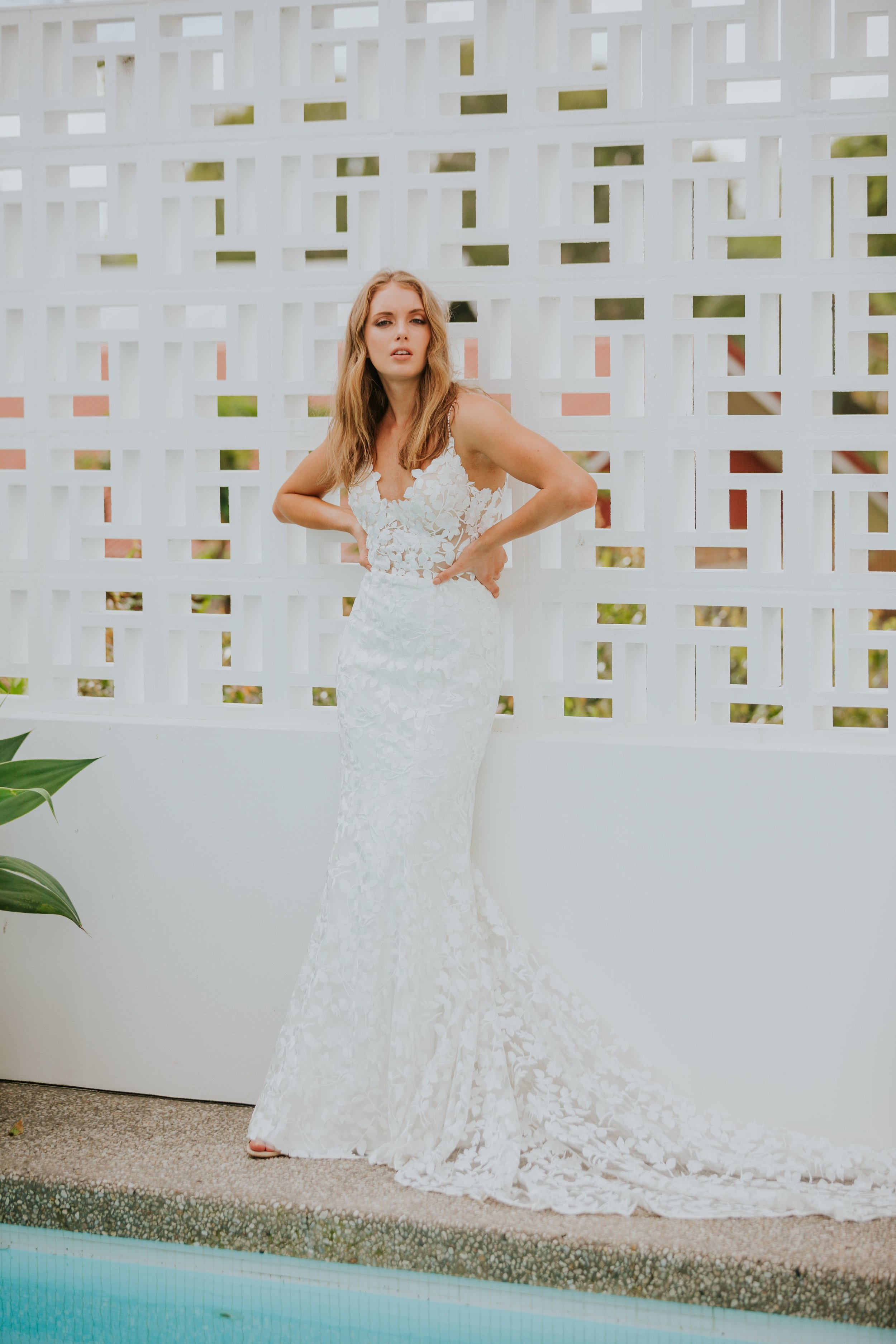Our BALI gown is the dress you put on and never want to take off again. Made cool, luxe bride using our exclusive ivory floral textured lace. Her heart-stopping detail is in the crystal embellished spaghetti straps that span over the shoulders and down a revealing open back.