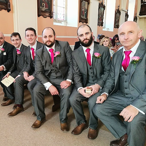 The Keegan Men sitting in grey suits at a wedding