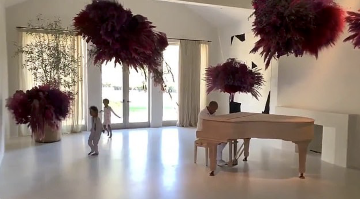 Kardashian children and rapper Kanye West occupy a room furnished with an elaborate floral installation.