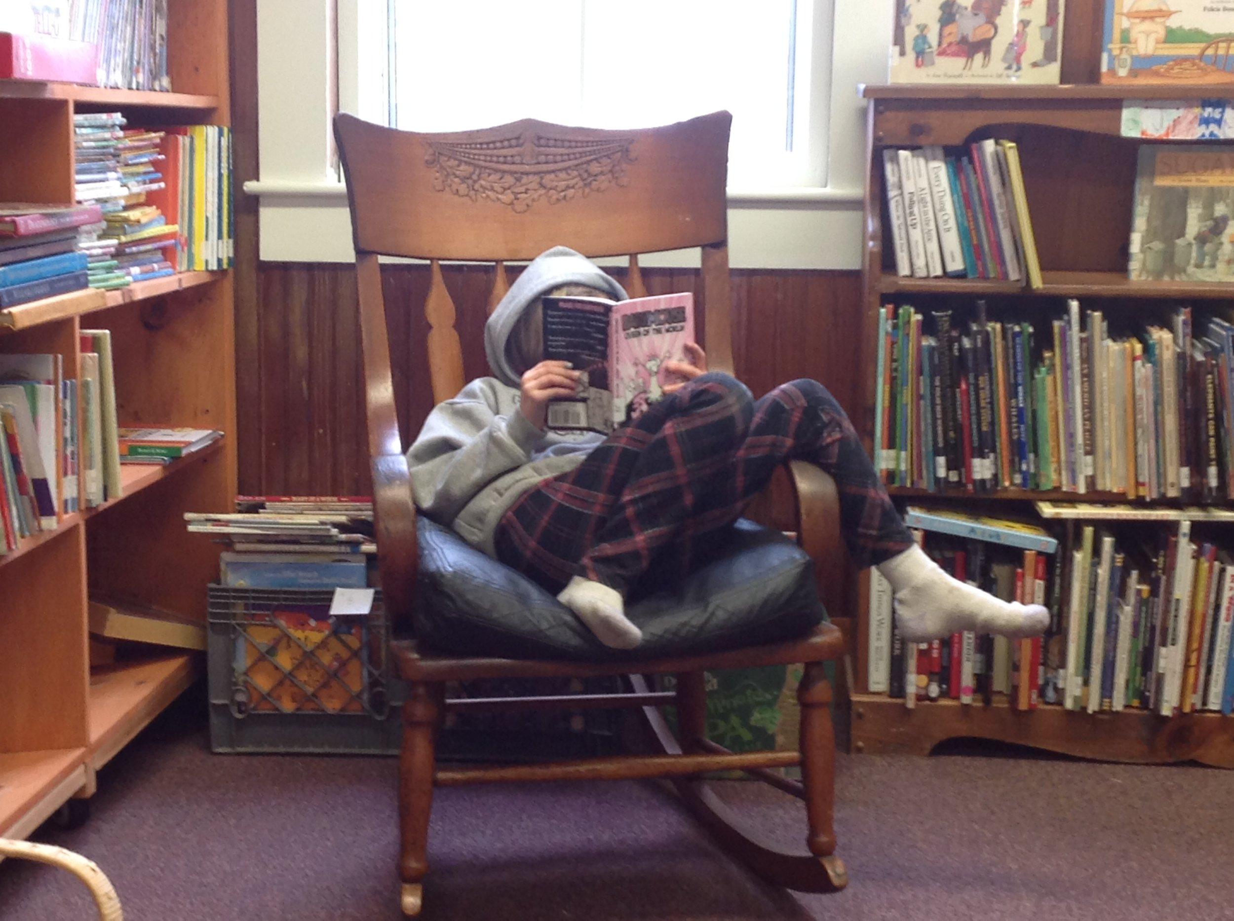A patron, reading her book in our cozy library seting.