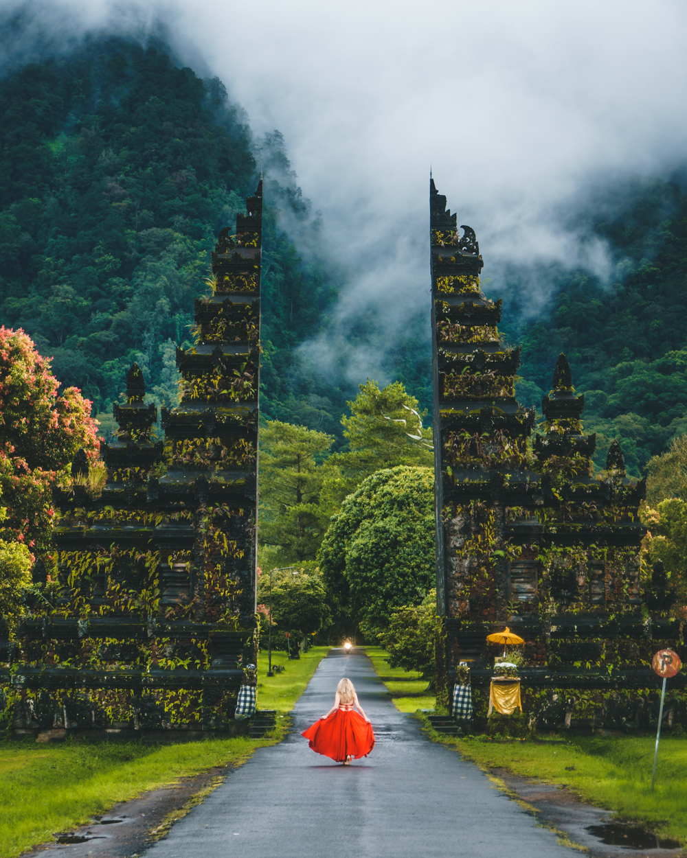 Photograph of a girl in a red dress running through what looks like a gate, formed by two pillars with a buddhist artistic style to them. Alongside the road she is running on, in the end of is a light formed by what looks like a motorbike. The surrounding is all green tropical forest and the vegetation has grown on tho the pillars making the red dress and the girl really stand out in the center of the frame. The photo is taken in portrait mode to get the full height of the pillars and incorporate the clouds that lay on top of the mountain in the background. The photograph is taken in Bali, Indonesia, 2018 by Oliver Sjöström.