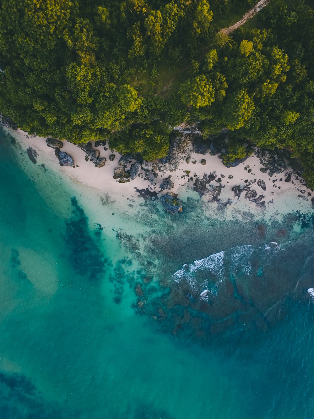 This drone capture of a beautiful coastline show the beautiful colors of nature. On the top of the frame is the green of the forest, whilst in the middle is the white sand that slowly fades into the light blue colors of the ocean. This photograph was taken in Indonesia, Bali, Padang Padang in 2018 By Oliver Sjöström, Ollivves