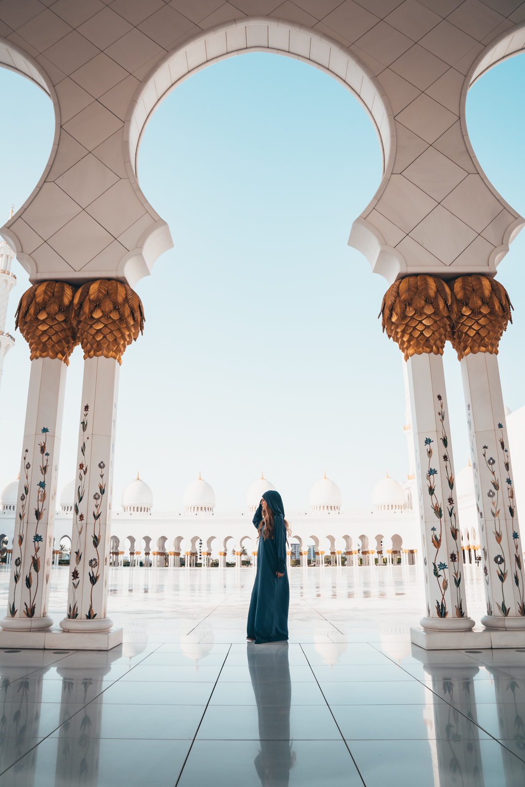 Photograph of a woman with a blue dress standing between two pillars in a white mosque with very unique and beautiful handcrafted architecture. This photograph was taken by Oliver Sjöström, ollivves, in Sheikh Zayed Mosque, Abu Dhabi, United Arab Emirates, 2018.