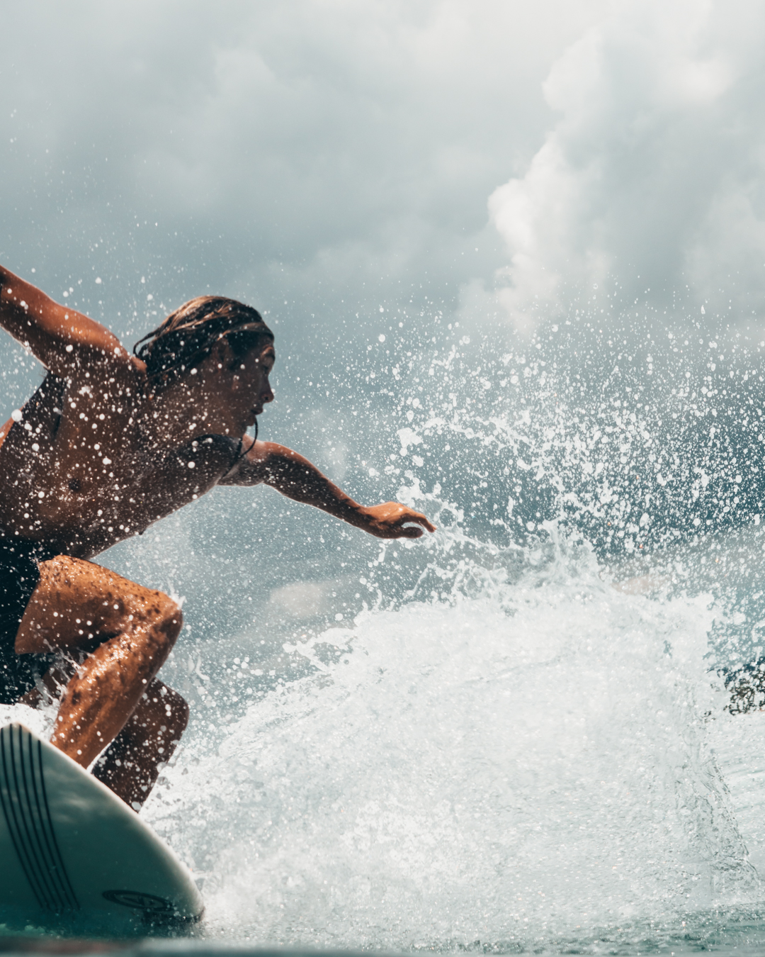 Close up photograph of surfer ripping through a wave. Water splashes around the surfer as he is turning the surfboard on the face of the wave. His long hair and tanned body covered with water forming like drops because of the speed he is coming at. Speed created by the force of the sea. He is holing out his arms to keep his balance. The photograph is taken from the water by Oliver Sjöström, Ollivves in Gerupuk, Lombok in 2018.