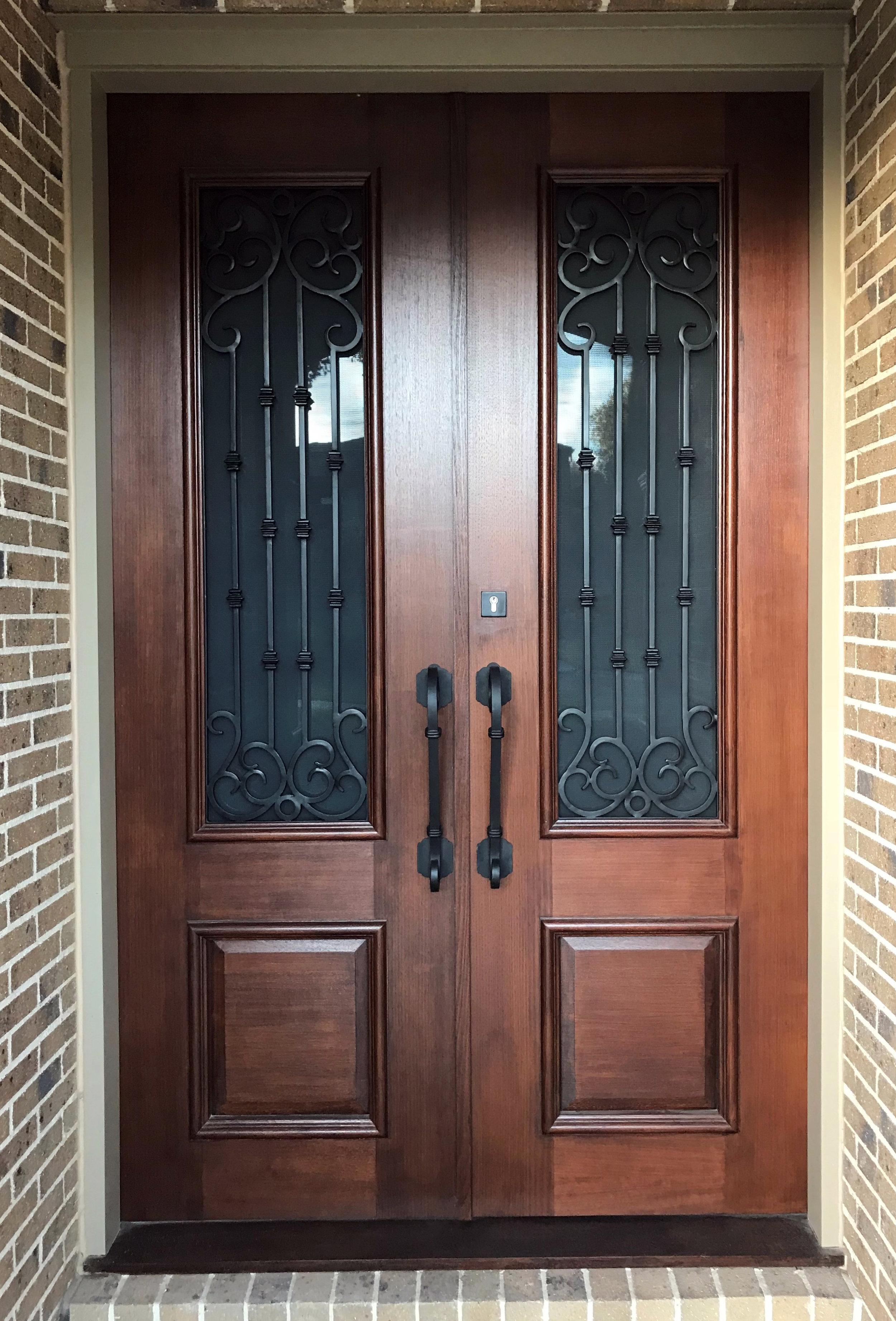 Picture of wooden door with Adoore Iron Designs Custom wrought iron door handle.