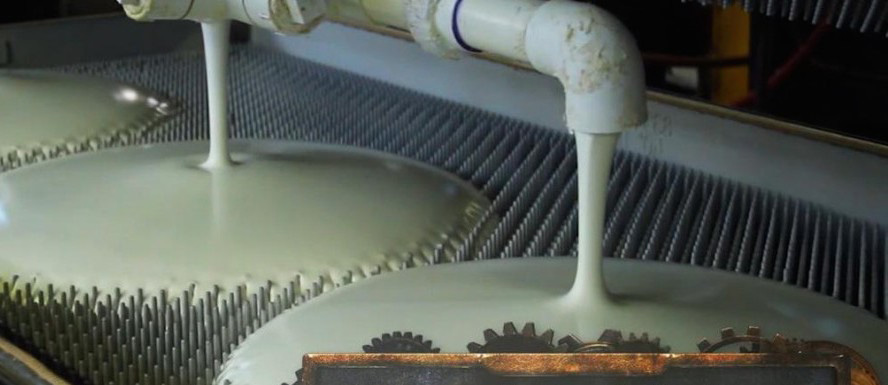 Liquid, botanically derived natural latex rubber being poured into mold trays, ready to be solidified into mattress blocks.