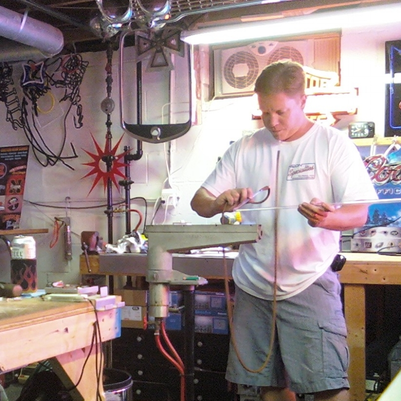Man blowing glass neon tubes