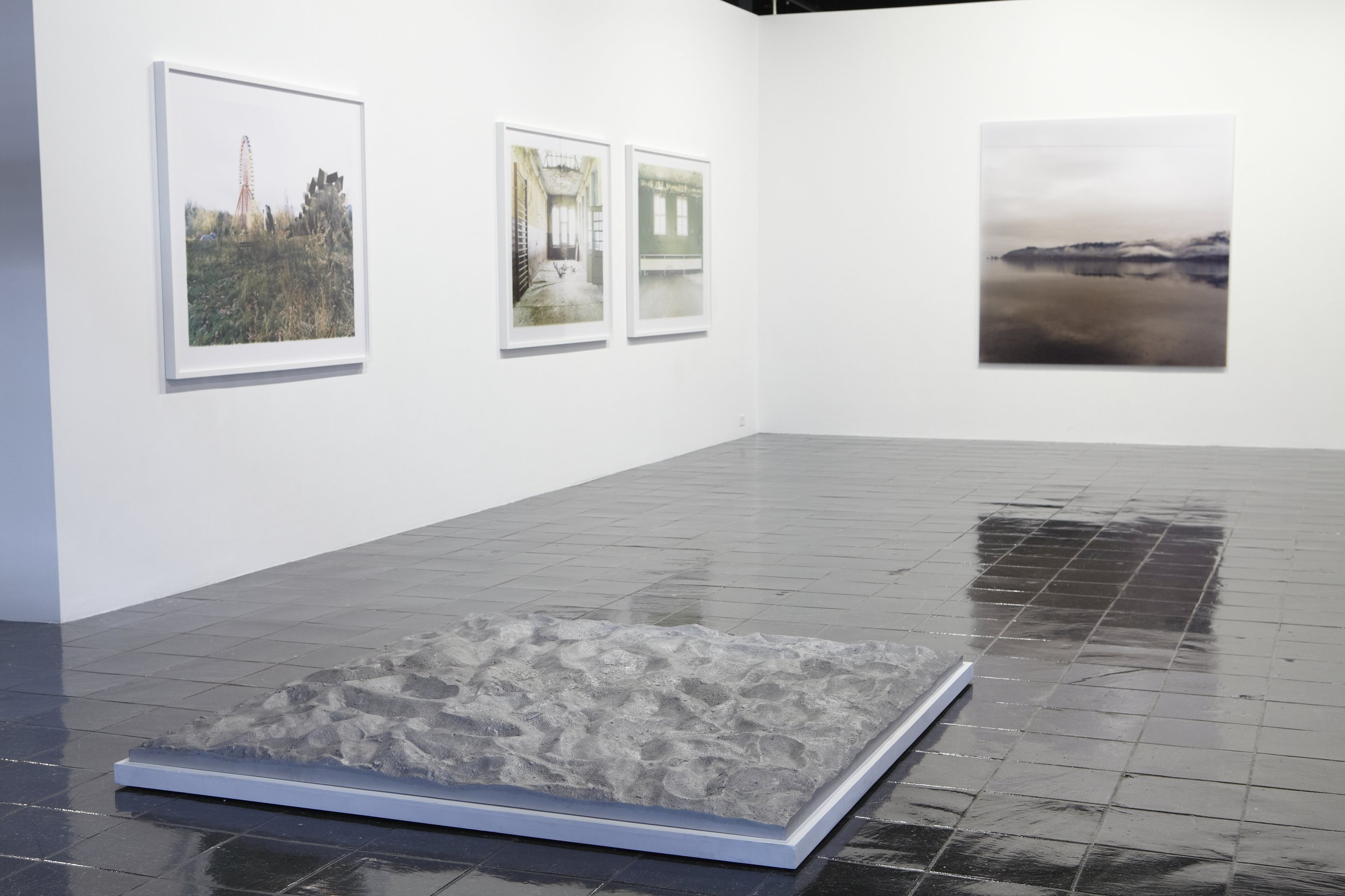 Sarah Schönfeld, from the series  Wende Gelände , 2007. C-print, 48 x 60 inches. Courtesy of the artist and Kunstagenten, Berlin. Installation view. Foreground: Michael Brown,  The People's Playground , 2008. Cast aluminum, 71.75 x 69 x 2 inches. Courtesy of the artist and Yvon Lambert Paris, New York, London.