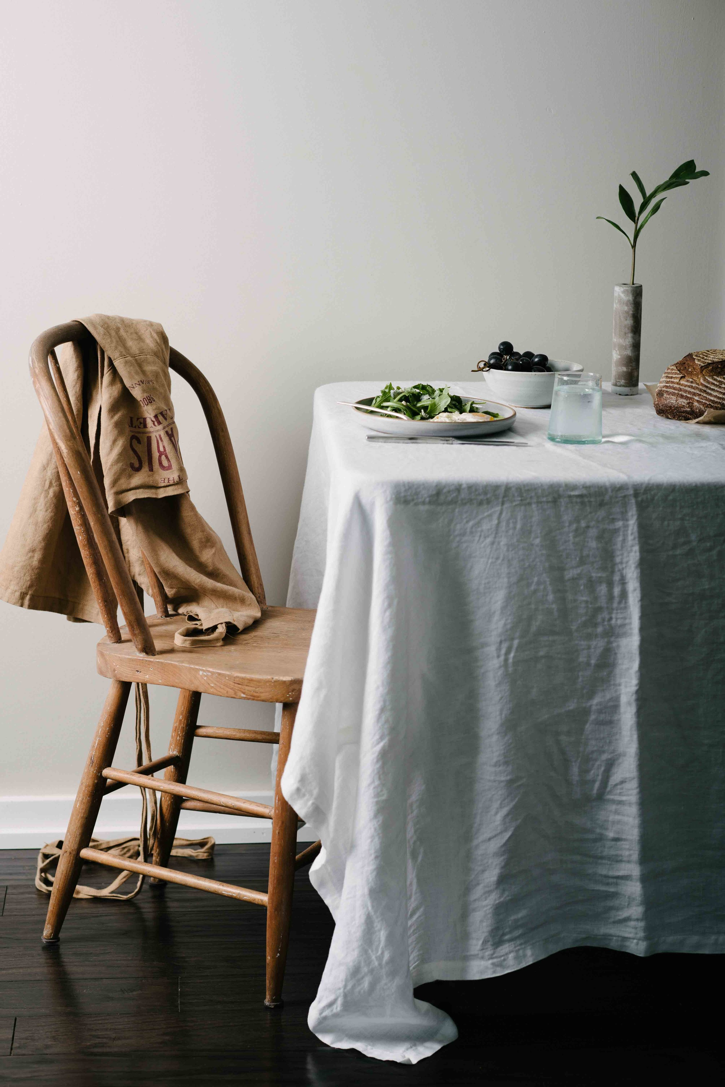 White Linen Covered Breakfast Table with Wooden Chair with Fried Egg, Salad, Grapes, and Bread