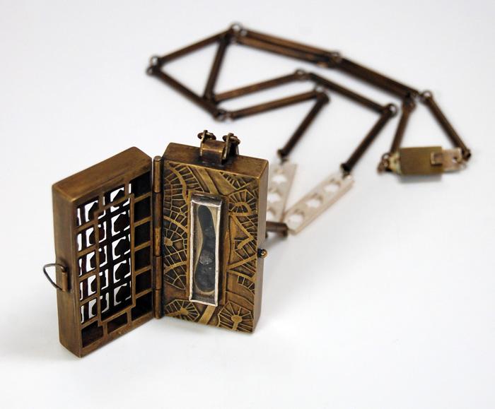 "Suburbanite's Reliquary,  brass, driveway asphalt, glass, silver, nickel silver, 2"" x 1"" x ½"" (locket), 2011"