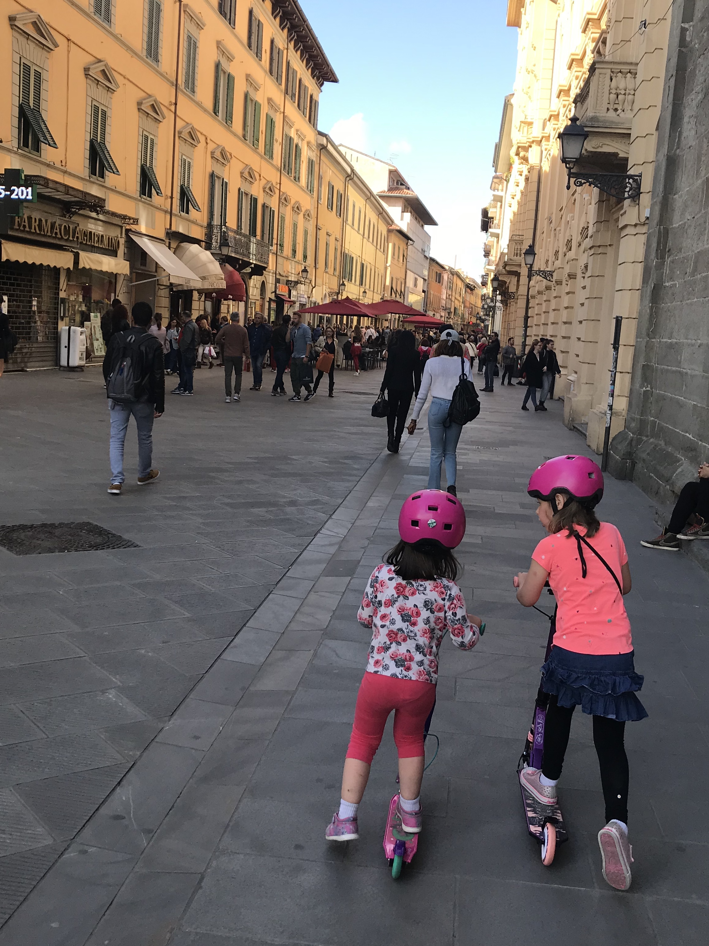 Our little ones riding their scooters in Pisa