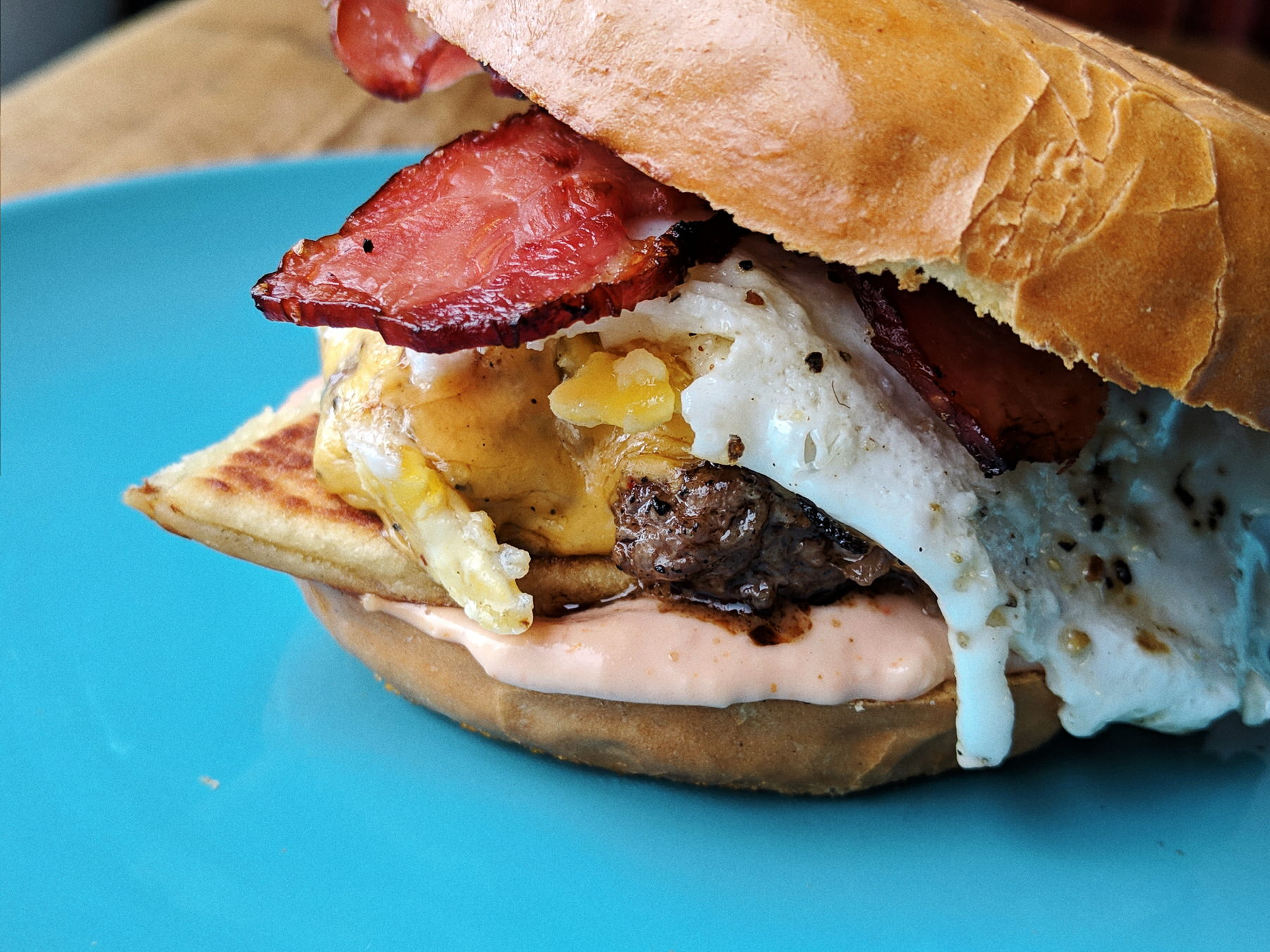 Our new Brunch Burger: cheeseburger, potato scone, fried egg and bacon on a bagel bun.
