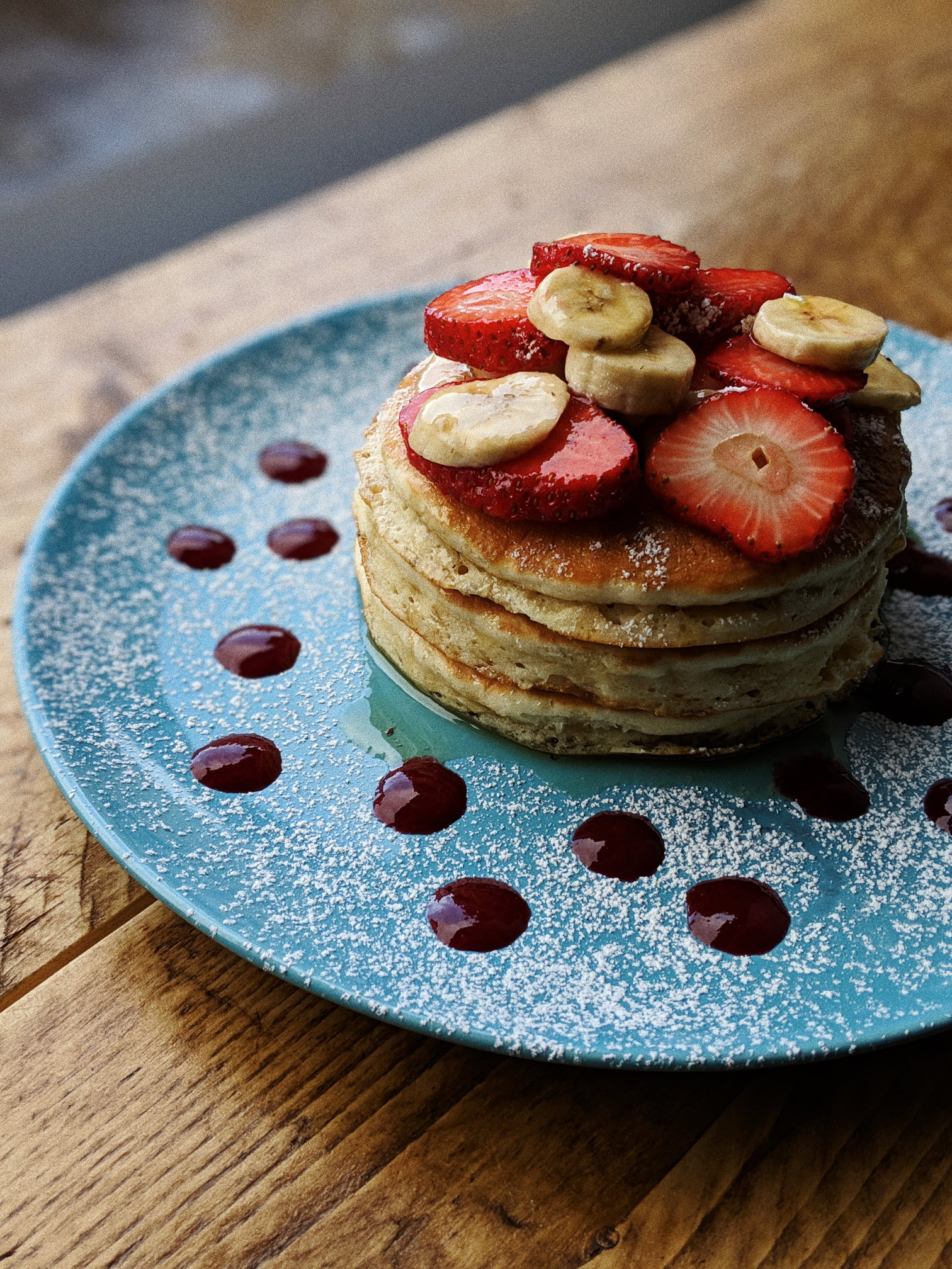 Pancake stack with strawberries, bananas, and maple syrup.