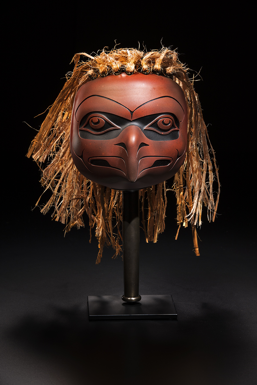 Preston Singletary (American Tlingit, born 1963).  Wealth – Eagle Rattle,  2013. Blown, hot-sculpted, and sand-carved glass, cedar bark; steel stand; 15 1/2 × 7 × 7 in. Courtesy of the artist. Image courtesy of Russell Johnson.