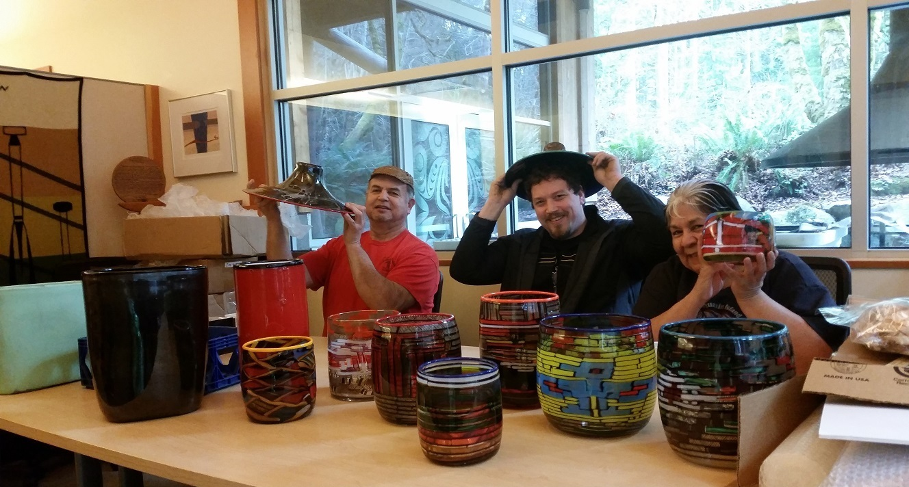 Artists, Delbert Miller (Skokomish), Dan Friday (Lummi), and Yvonne Peterson (Chehalis) with vessels made of glass cane that reflect adaptations of their own familiar basketry designs. Photo courtesy of the Evergreen Longhouse.