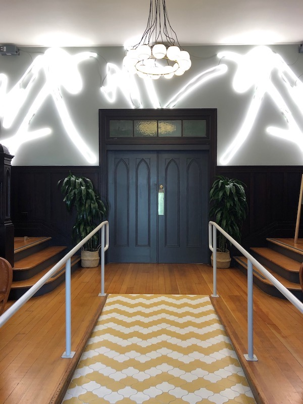 The entryway to The Assembly with custom neon design by a local female artist.