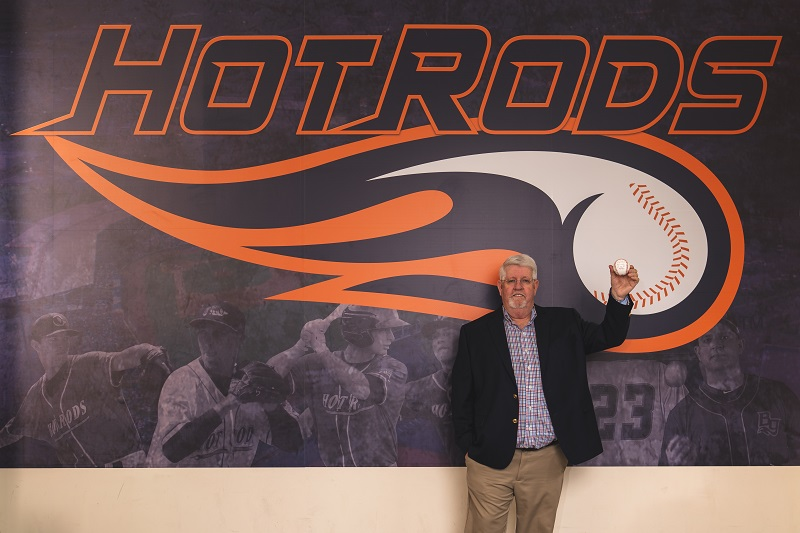 AJ holding a signed baseball in front of the Hot Rods offices.