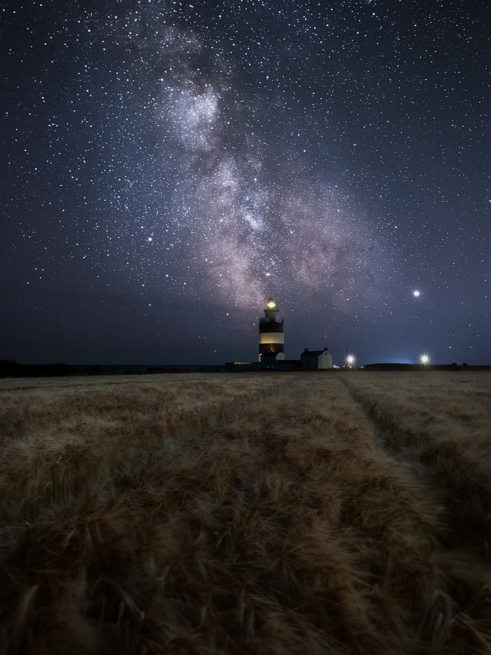 Milky Way rising over Hook Head lighthouse in Co Wexford. This is the oldest operational lighthouse in the whole world. I love golden wheat fields and even though I knew they would be all blurred in this shot I did not care, the tractor drill gives this shot the perfect leading line to the lighthouse and the Milky Way. This was one of the trickier blends due to the buildings. When shooting my foreground I dialled down the aperture for one exposure to get the starburst from the lights.