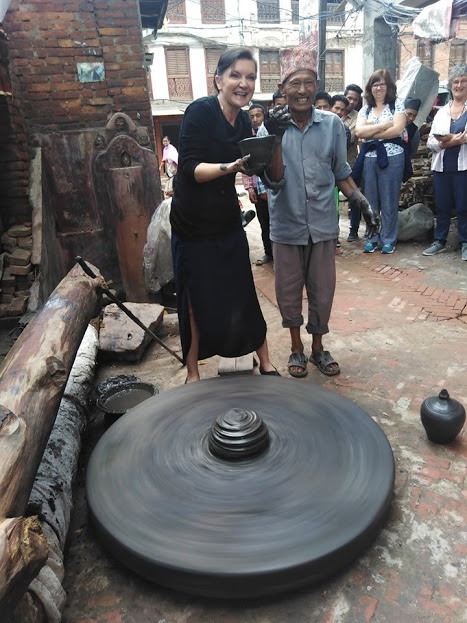 Our traveller getting hands on with the pottery wheel!