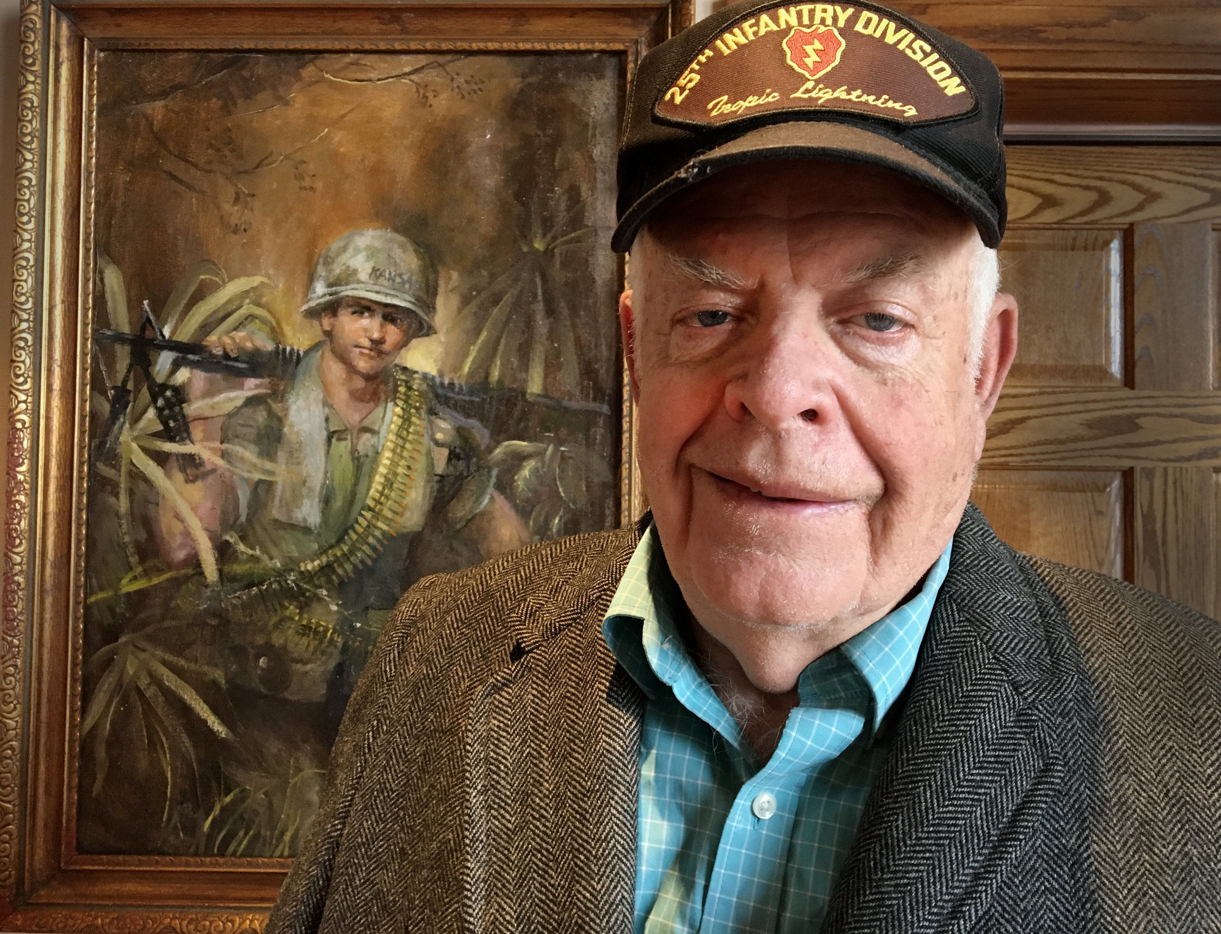 Jim Nelson with one of his original paintings, currently on display at Missouri's National Veteran's Memorial. Photo: Sean Loftin