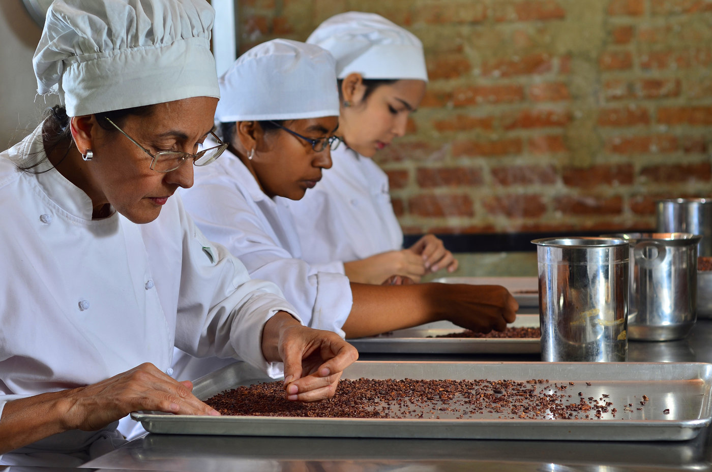 Entrepreneurs sort cocoa beans on a tray at Cacao de Origen, a school founded by Maria Di Giacobbe to train Venezuelan women in the making of premium chocolate. Courtesy Cacao de Origen.