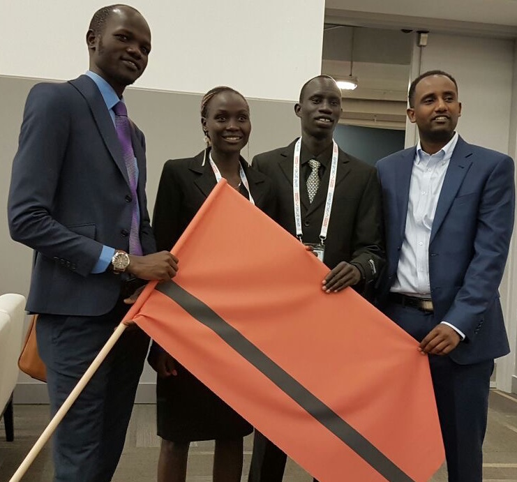 James Madhier with 2016 refugee olympians, holding the Refugee Flag of Hope.