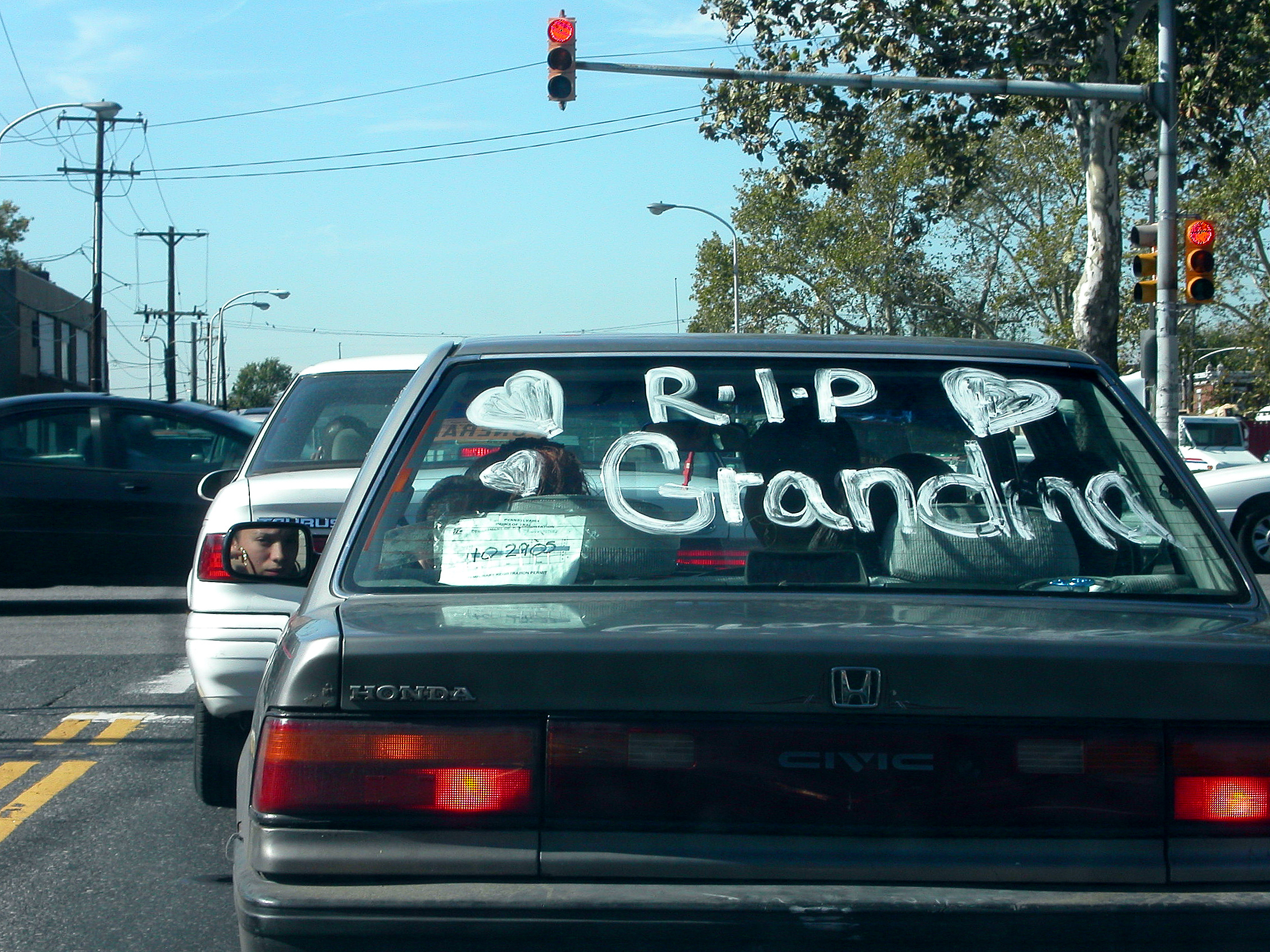 "windshield memorials - ""Wherever I go, she knows I'm thinking of her.""  That was the response of a car owner when asked why he placed a memorial decal on his car.  These Windshield Memorials, often found in Latino communities, are one of the many examples of cultural public displays of grief.  Some are written with large glass paint markers, an immediate response to the loss.  Others are designed with permanent decals, whose graphic designs are often expressions of clip-art and folk art.  Most of the Windshield Memorials obscure the rear view, thereby ignoring the risk to the driver.  As demonstrated by the August entry, sometimes room is set aside for another loss (as on a grave monument) despite the impermanence of the vehicle.  This is an insight into an industry, one that is largely devoid of trained graphic designers.Click on the image for more"