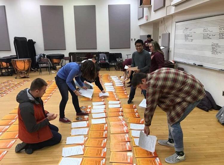 Members of Kappa Kappa Psi filling music folders; Source: Nate Carneal