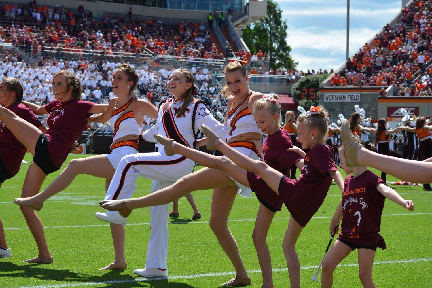 Former Drum Major Jenna Sharer, feature twirlers Kaitlyn Boyer and Serena Bronk, and lots of little twirlers for the day join us in dancing along to the Hokie Pokie during halftime; Source:  Facebook