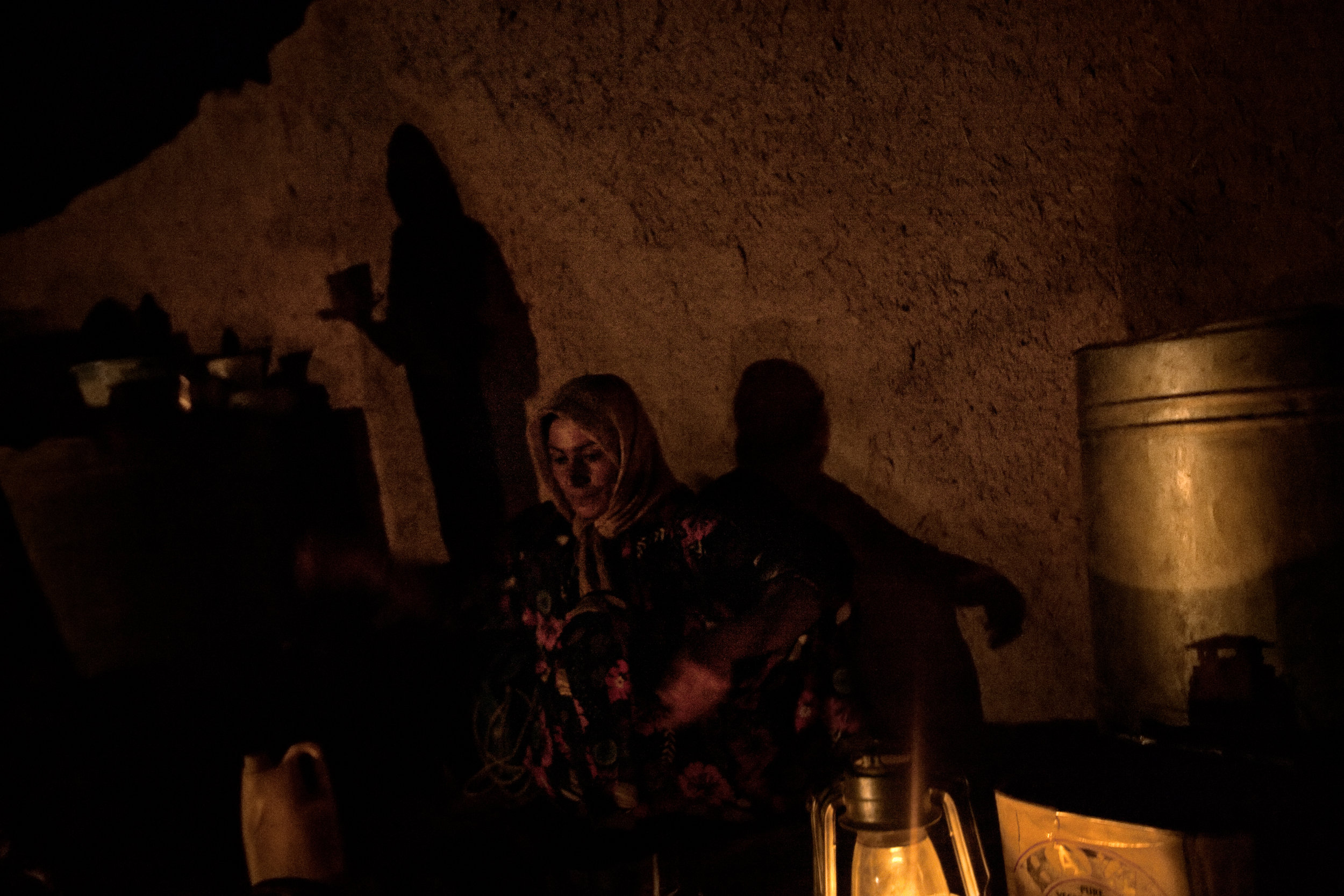 Kharaman Ibrahim Mohammed washes dishes by the light of a lantern in Showara, Kifree District, Kurdistan, Iraq on July 3, 2010.