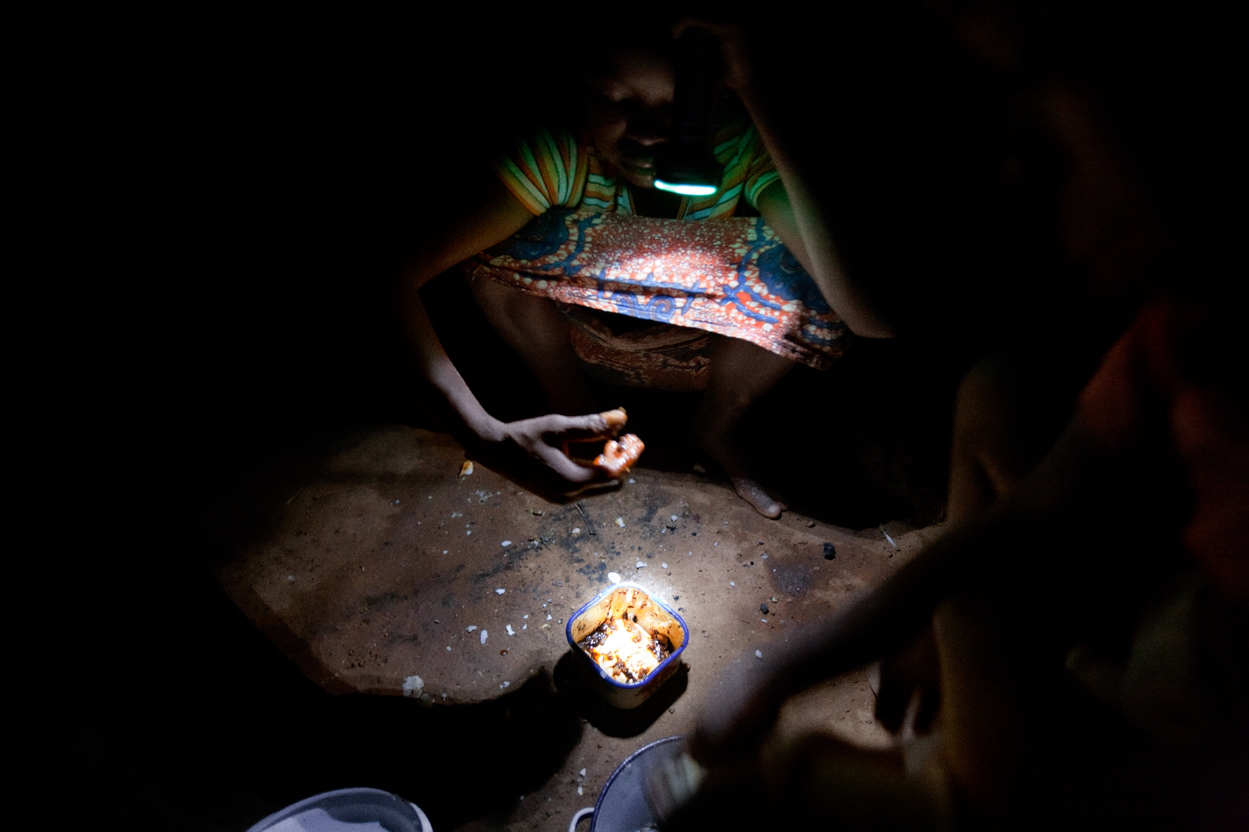 A young girl eats dinner in her home in Voggu, Northern Region, Ghana, on Nov. 17, 2009.