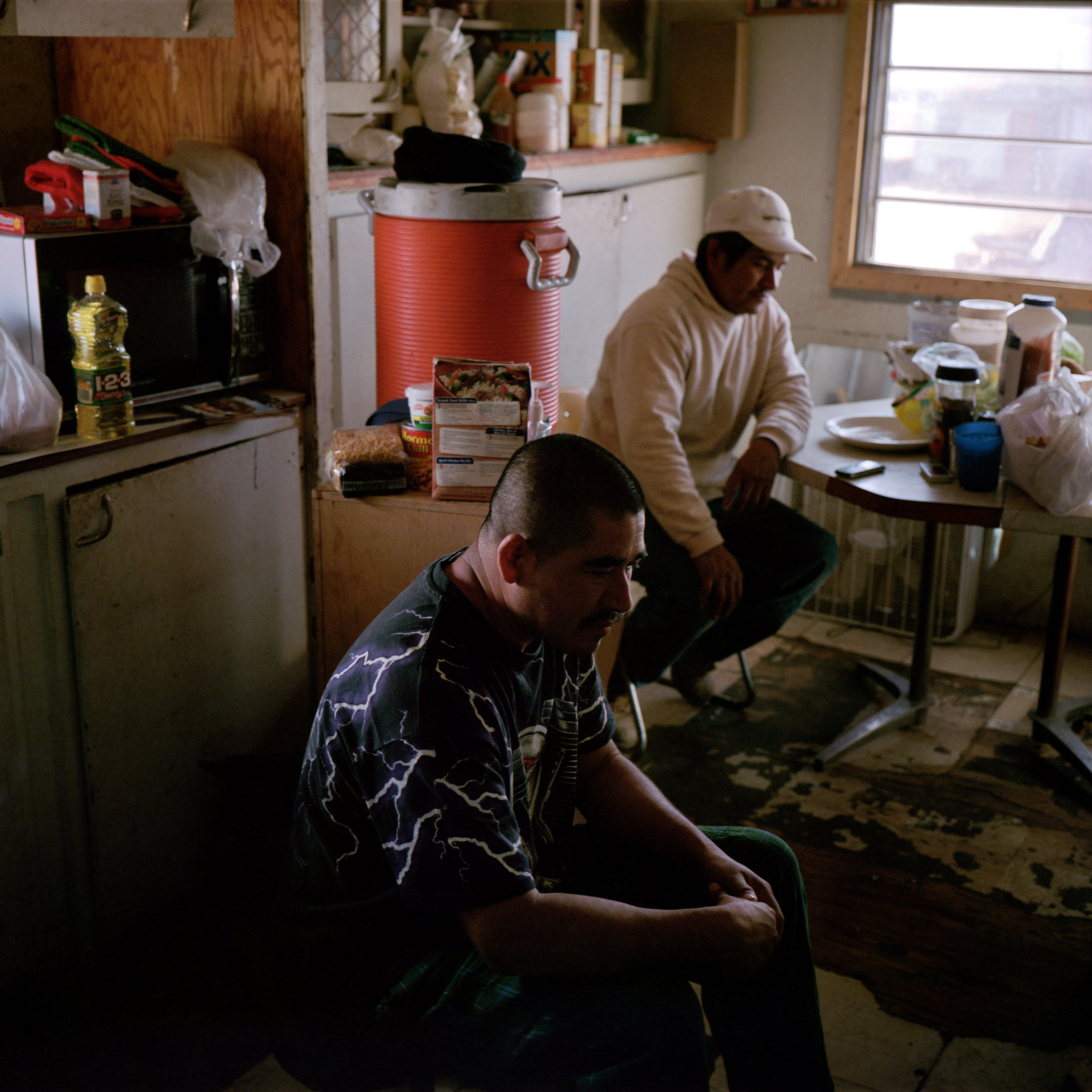 Isidro Alcudia, front, and his brother Epifanio wait in the early morning for a call offering them work as day-laborers in their trailer in Pajarito Mesa, New Mexico, USA on Feb. 17, 2011. The two work primarily in construction, but fewer people are building as a result of the global recession. They were not offered work on this day.