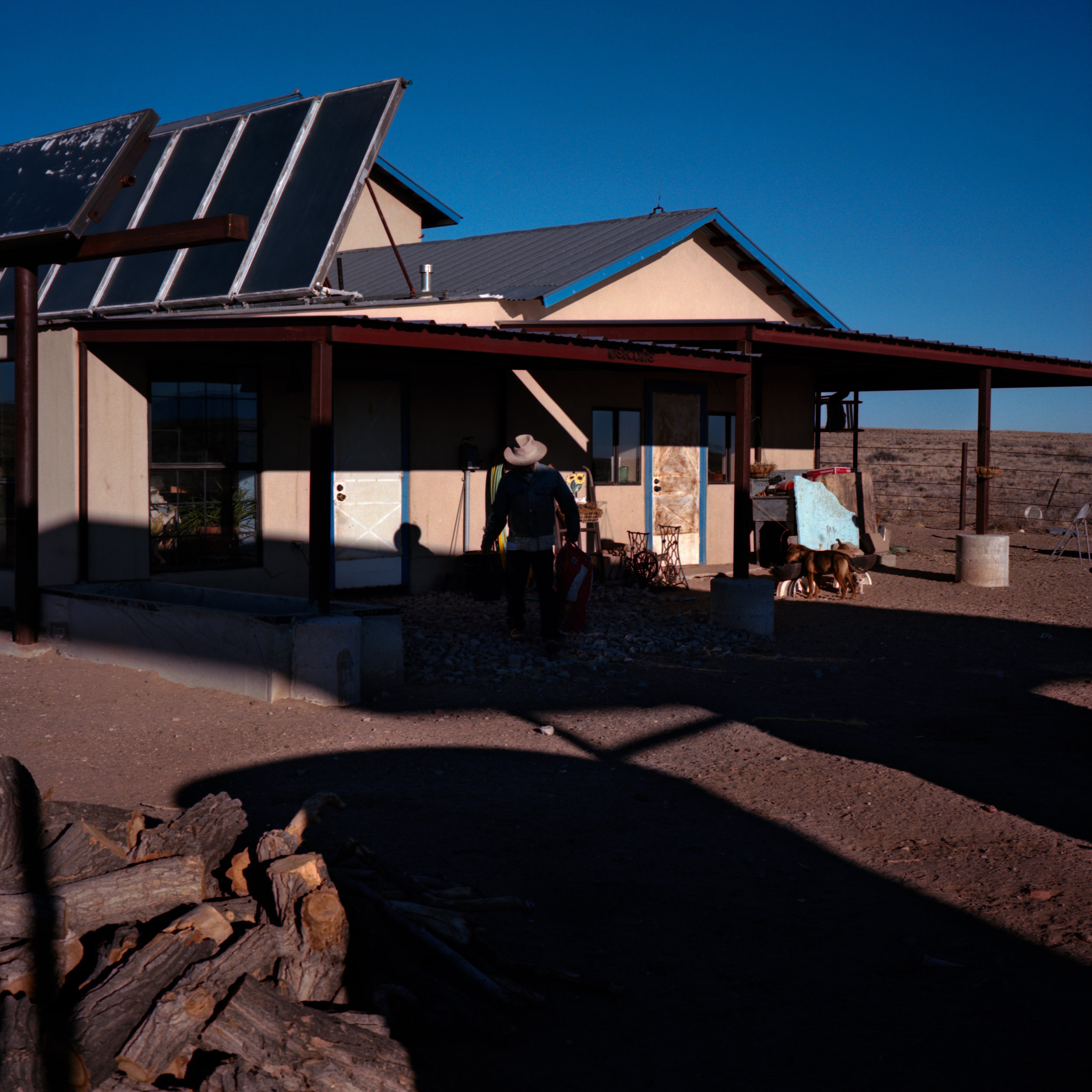 """Carlos Proffit outside of his home in Pajarito Mesa, New Mexico, USA on Feb. 15, 2011. Mr. Proffit moved to the Mesa """"to escape the rent cycle,"""" and then built his own home. He slowly learned to install and in some cases build solar and wind solutions for his home over the course of many years."""