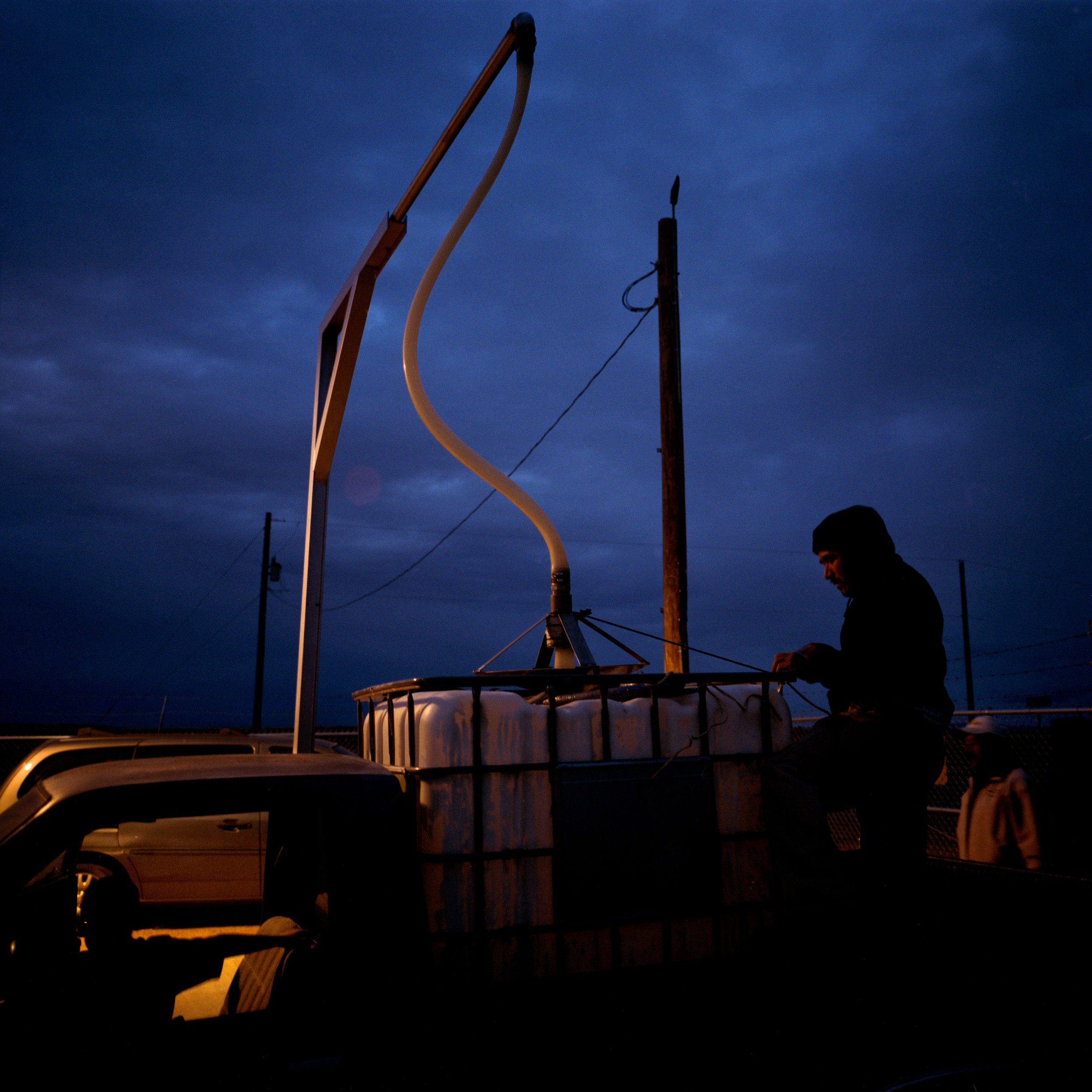 Isidro Alcudia fills a container with water from a pump that was installed at the base the Pajarito Mesa, New Mexico, USA on Feb. 18 2011. The pump is powered by the last power line before the Mesa. Members of the community haul their water from a pump that the city provided after a decade-long search for funding and permission.