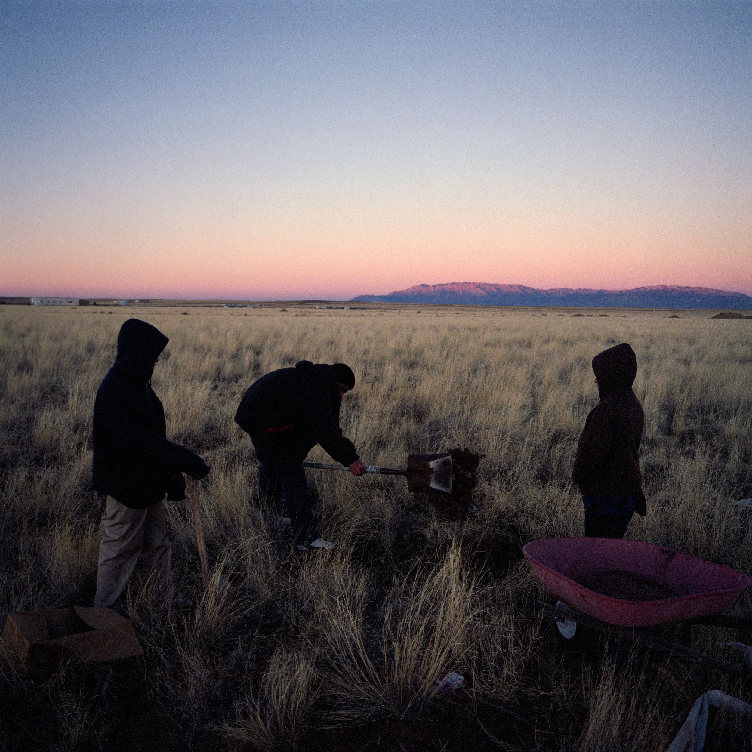 Members of the Alcudia family bury a deceased pet dog outside of their home in Pajarito Mesa, New Mexico, Feb. 9, 2011.