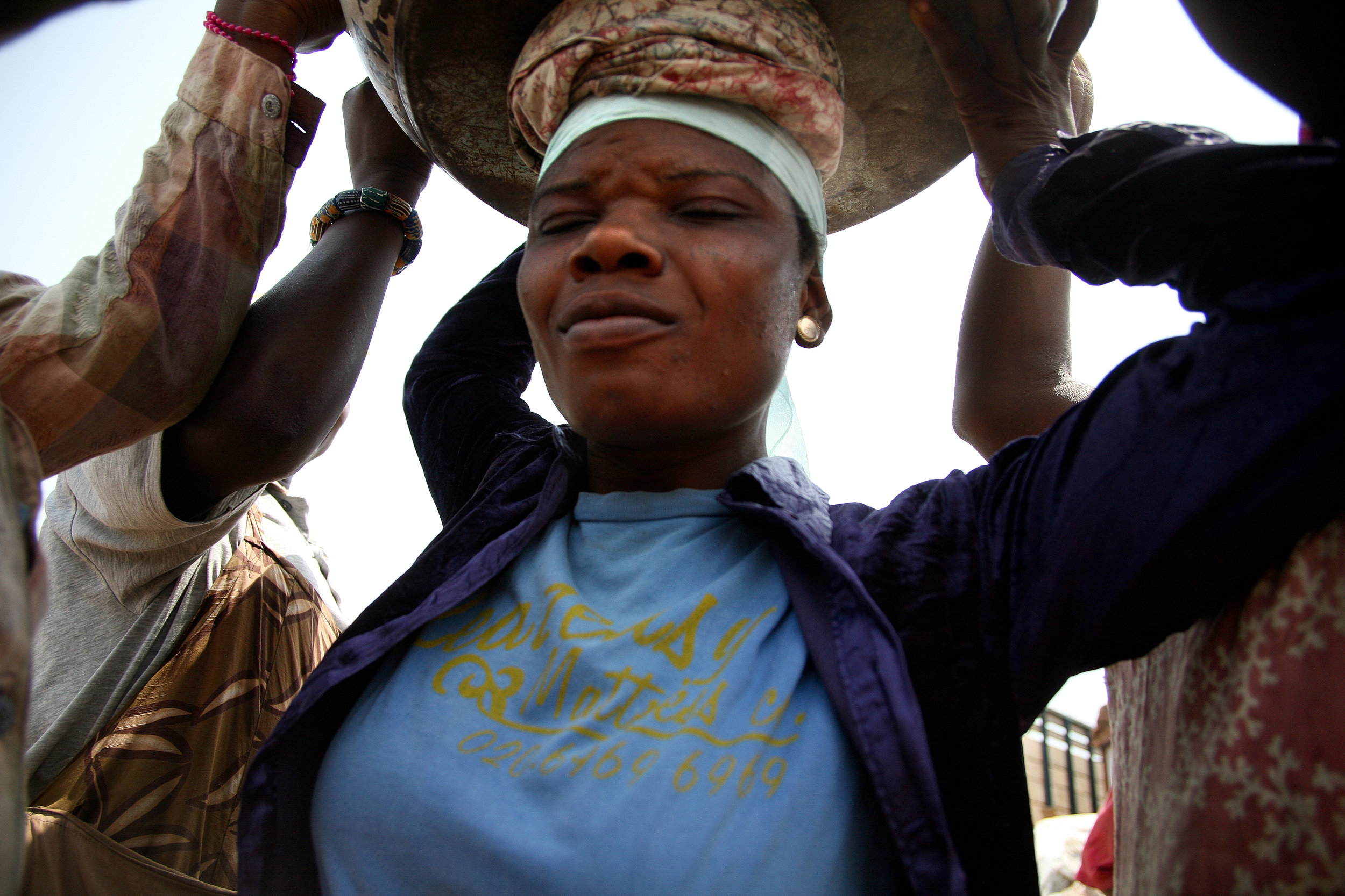 """Lamisi lifts a load of yams onto her head in Agbogblushie Market in Accra, Ghana on Feb, 13, 2009. """"At the end of the day, your whole body will be paining you,"""" she says of the work."""