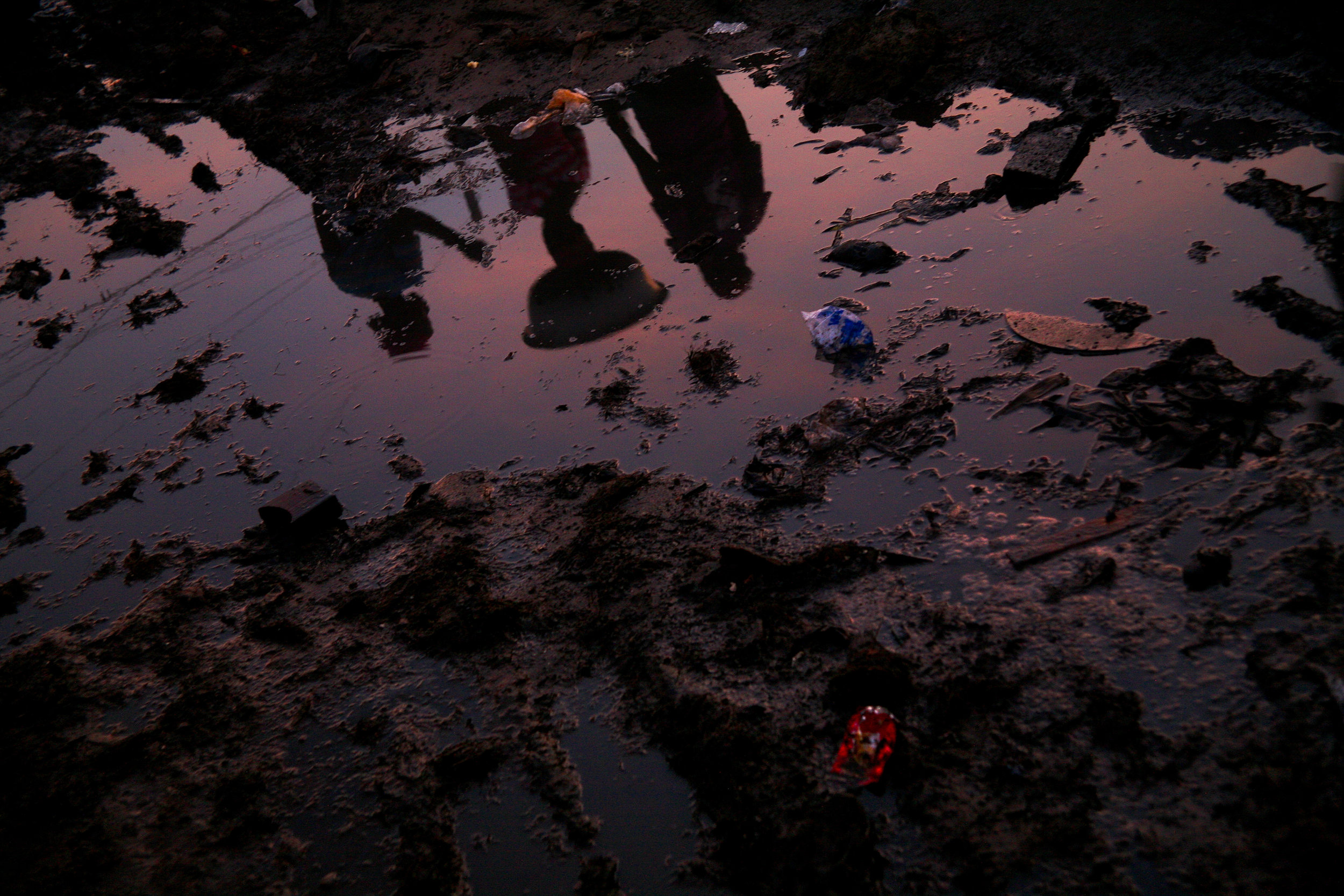 Kayayo girls reflected in the muddy pathways of the Old Fadama slum after a rainstorm in Accra, Ghana on April 14, 2009. The area has become a haven for northerners in the capital city, and each northern tribe has a small neighborhood of shacks and semi-permanent buildings.