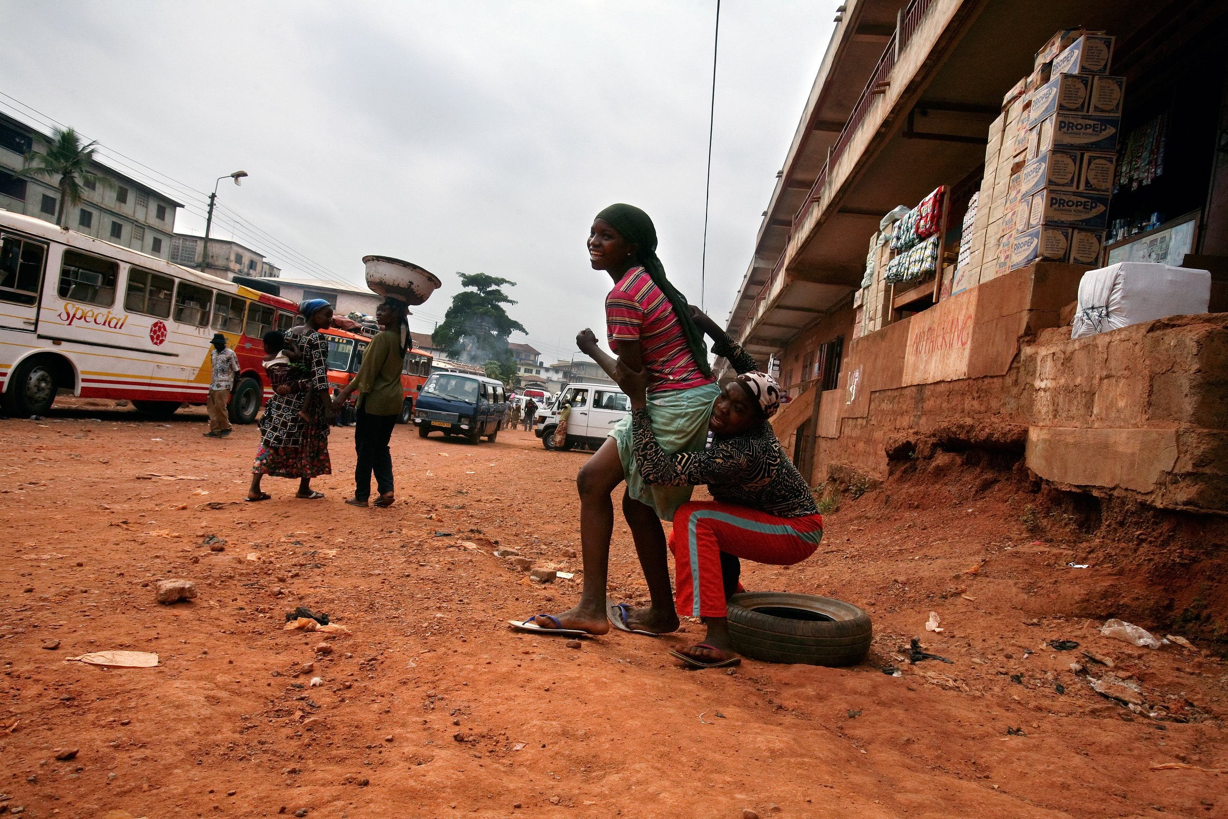 Teenage Kayayo girls rush to their feet to chase after a bus entering Doctor Mensah Market in Kumasi, Ghana, Feb. 26, 2009.