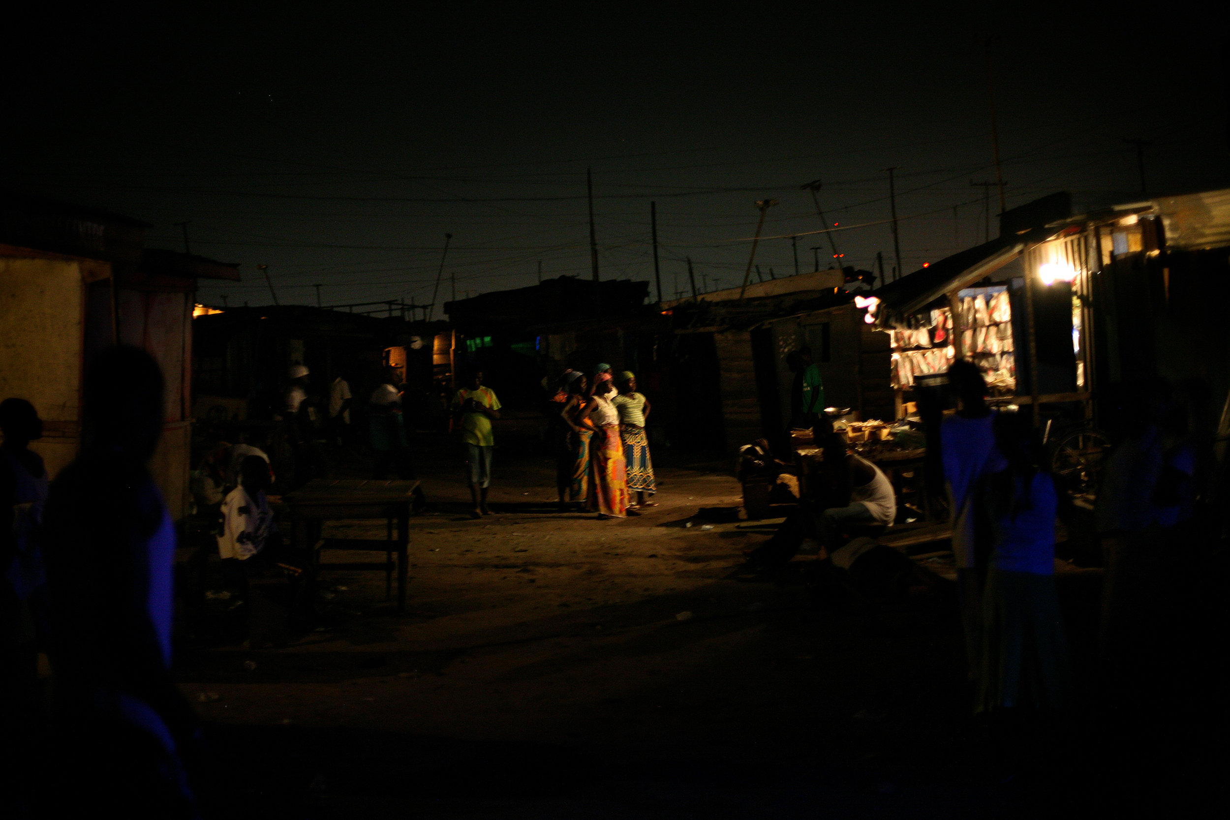 Kayayo girls watch a film playing in the midst of Old Fadama slum, where they live in Accra,  Ghana on March 14, 2009.