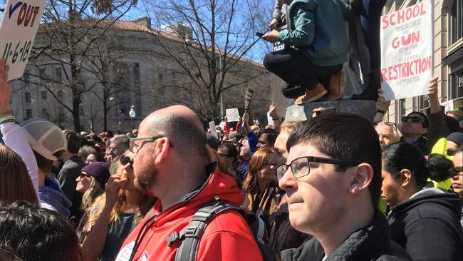 Benjamin Paley, a Sandy Hook survivor and high school freshman, takes in the March for Our Lives next to his dad, Andrew Paley. (Rebeccca Lurye)