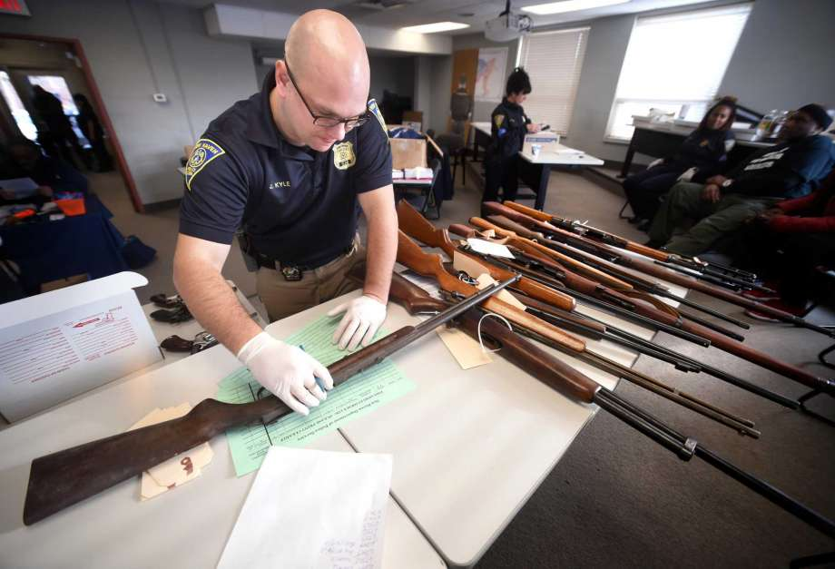 Detective Josh Kyle examines a rifle brought in during a gun buy-back at the New Haven Police Academy in New Haven on December 16, 2017.