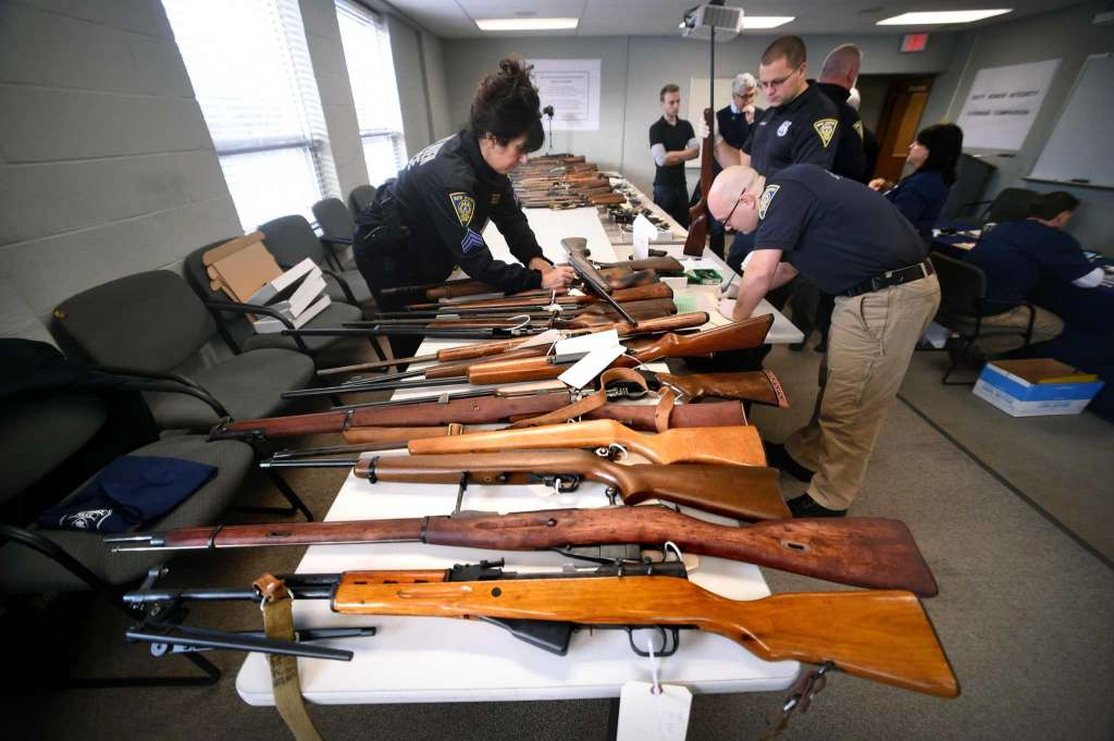 Guns brought in for a buy-back at the New Haven Police Academy in New Haven are catalogued on December 16, 2017.