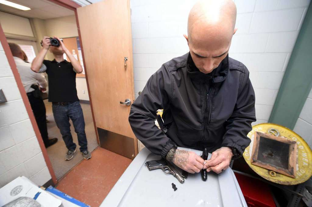 Volunteer photographer Adam Kuhn (left) takes photographs of New Haven Police Officer Jason Salgado making sure a handgun is not loaded during a gun buy-back at the New Haven Police Academy in New Haven on December 16, 2017.