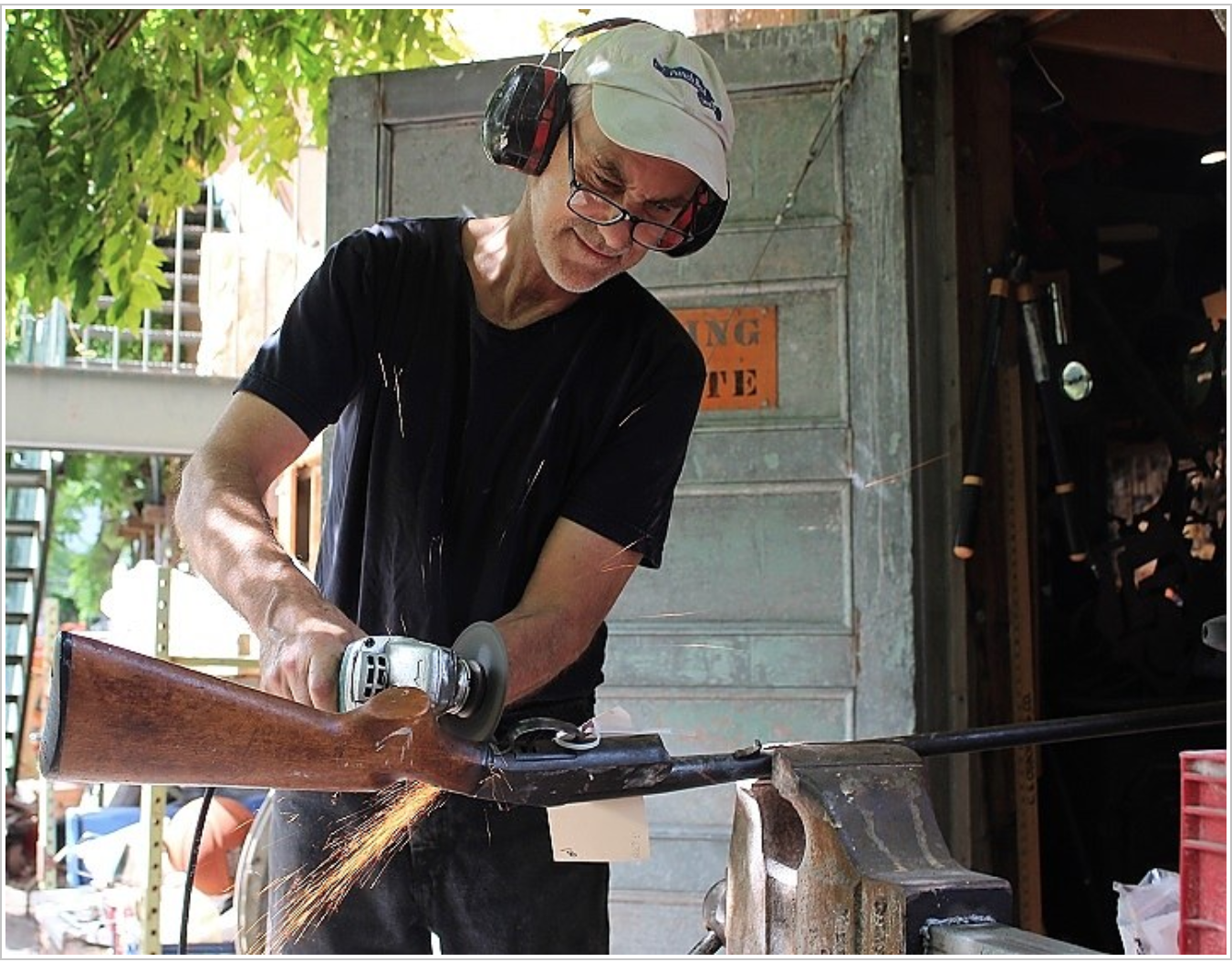 Local sculptor Gar Waterman tears into a donated gun in the garden behind his Westville studio on Monday morning.